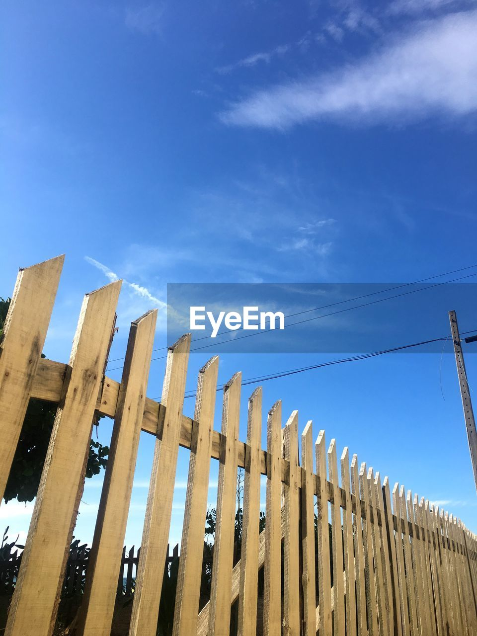 sky, low angle view, barrier, fence, blue, boundary, cloud - sky, wood - material, day, nature, no people, built structure, architecture, sunlight, security, protection, safety, in a row, outdoors, building exterior