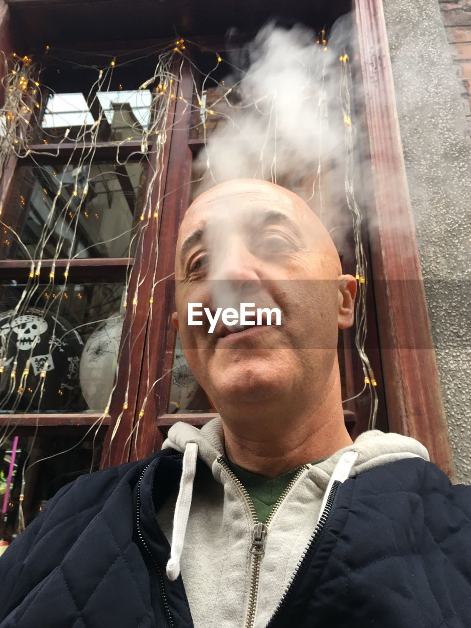 Low angle view of bald man exhaling smoke against window