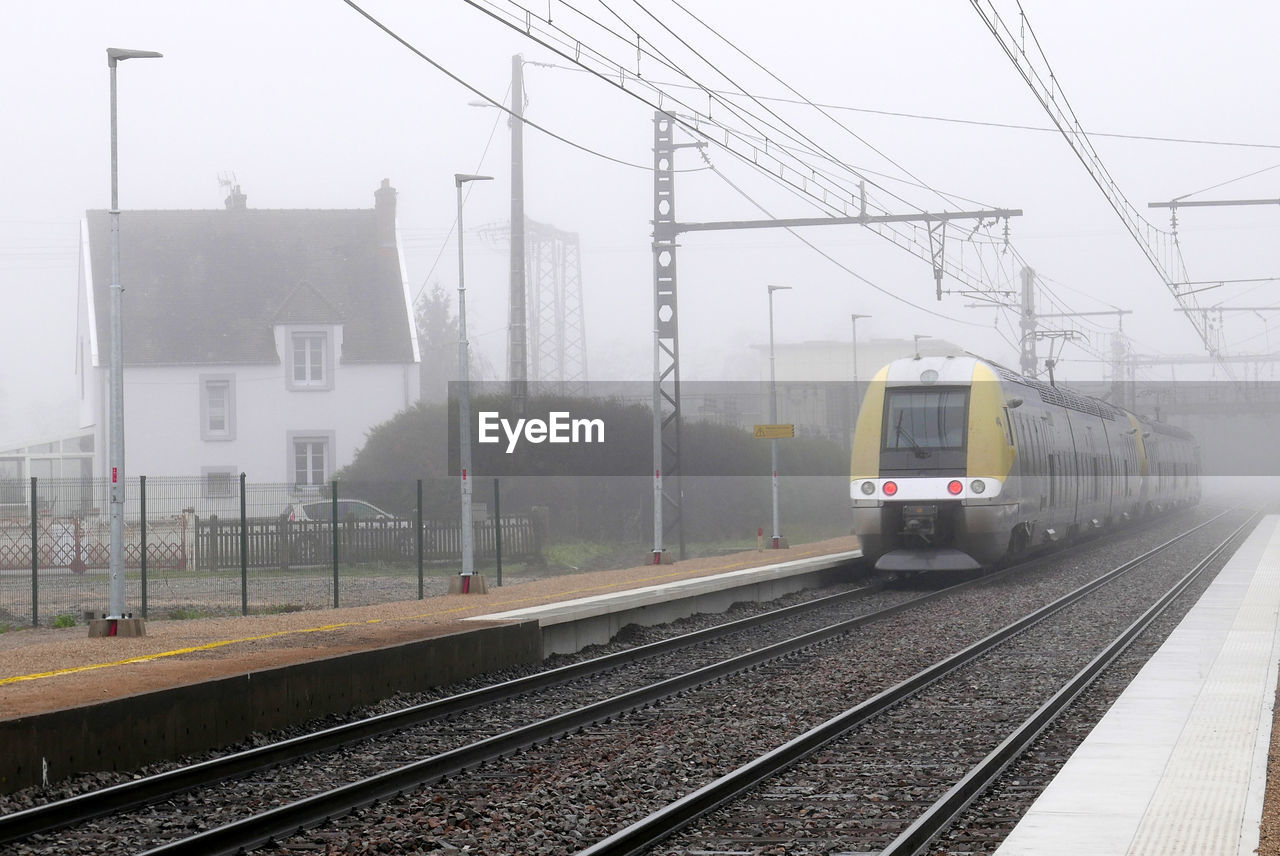 Train Arriving At Railroad Station Against Sky During Foggy Weather