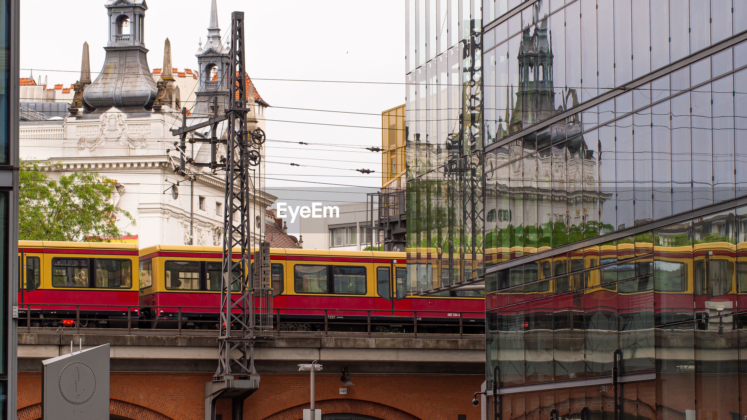 TRAIN ON RAILROAD TRACKS IN CITY AGAINST CLEAR SKY