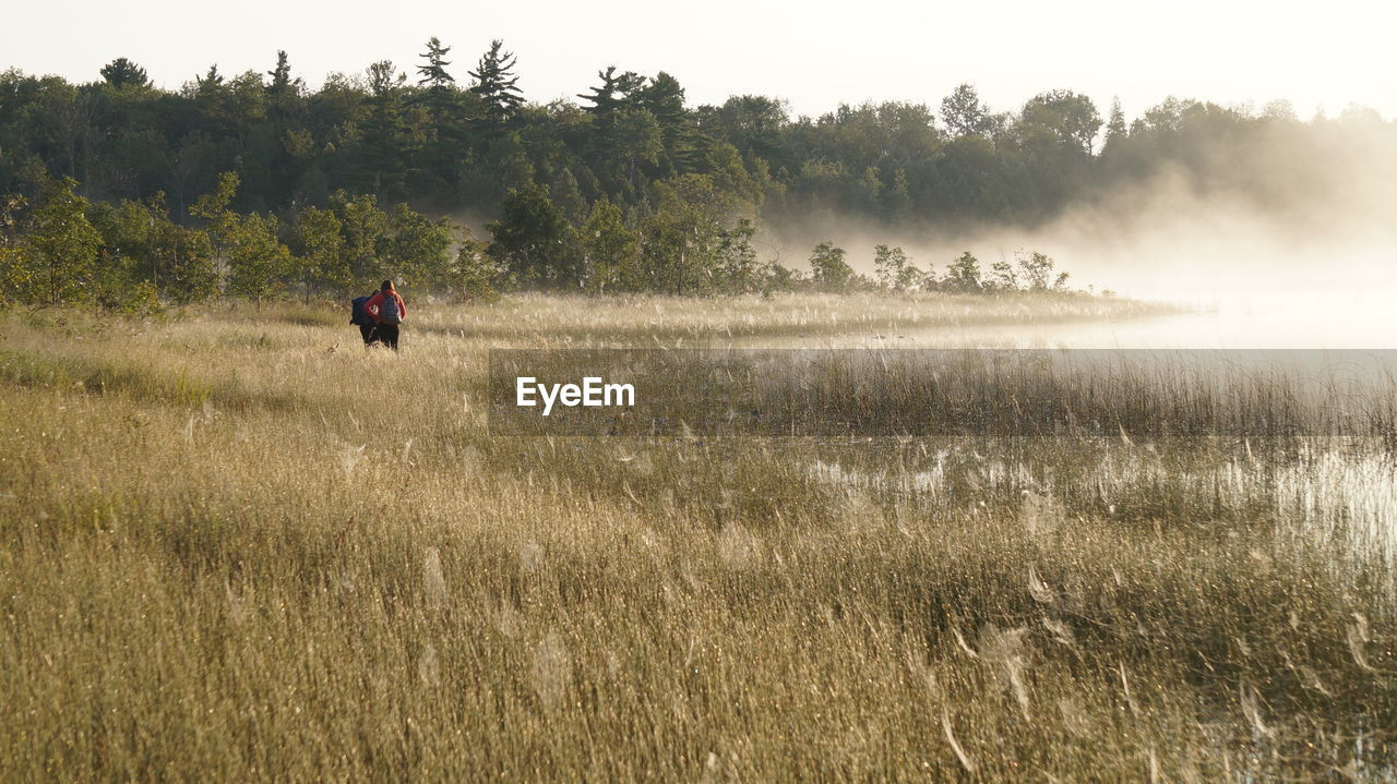 Friends standing on grassy field during foggy weather