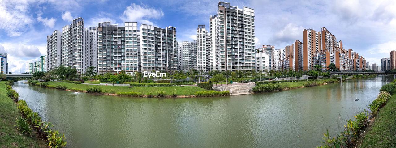 RIVER BY MODERN BUILDINGS AGAINST SKY
