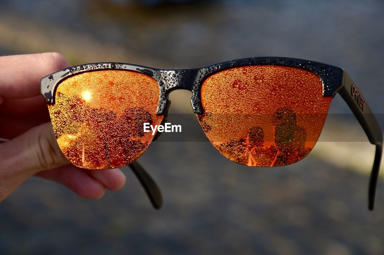CLOSE-UP OF HAND HOLDING SUNGLASSES WITH ORANGE