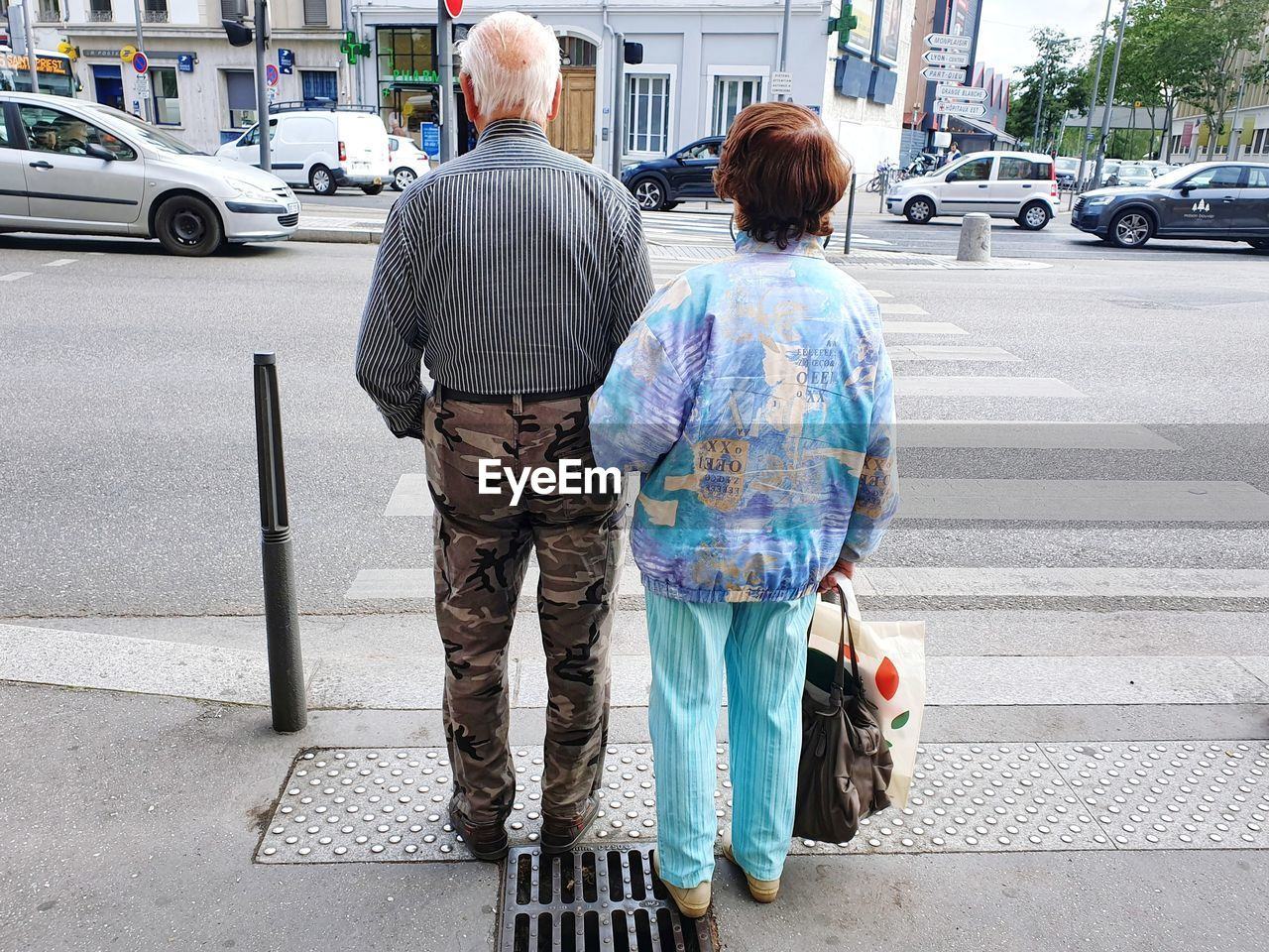 rear view, motor vehicle, car, city, street, transportation, mode of transportation, two people, women, senior adult, senior women, road, land vehicle, adult, men, casual clothing, real people, togetherness, day, senior couple, positive emotion, couple - relationship, outdoors