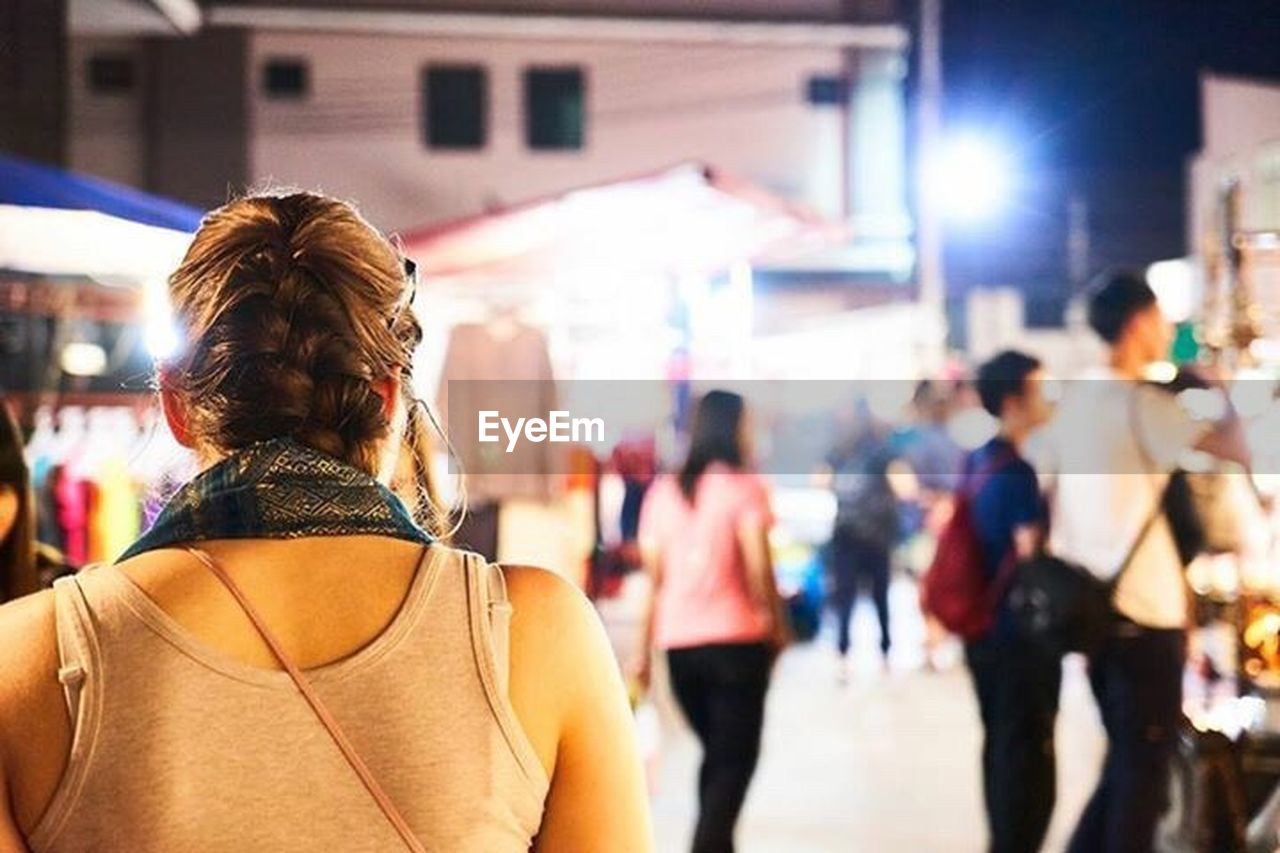 rear view, city, adult, architecture, focus on foreground, street, women, building exterior, incidental people, people, walking, city life, crowd, built structure, lifestyles, hairstyle, real people, portrait, casual clothing