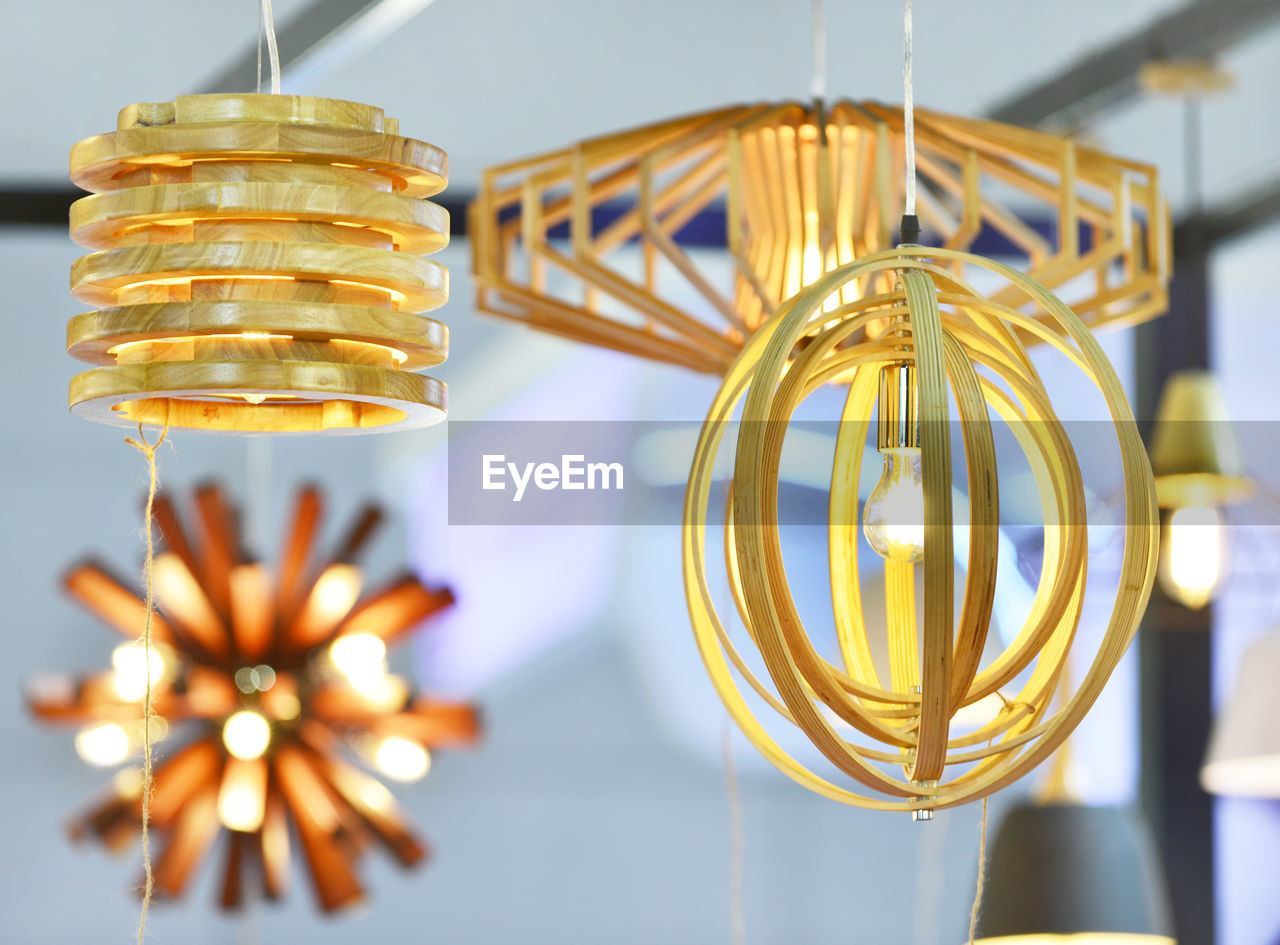 Close-up of various illuminated pendant lights hanging from ceiling