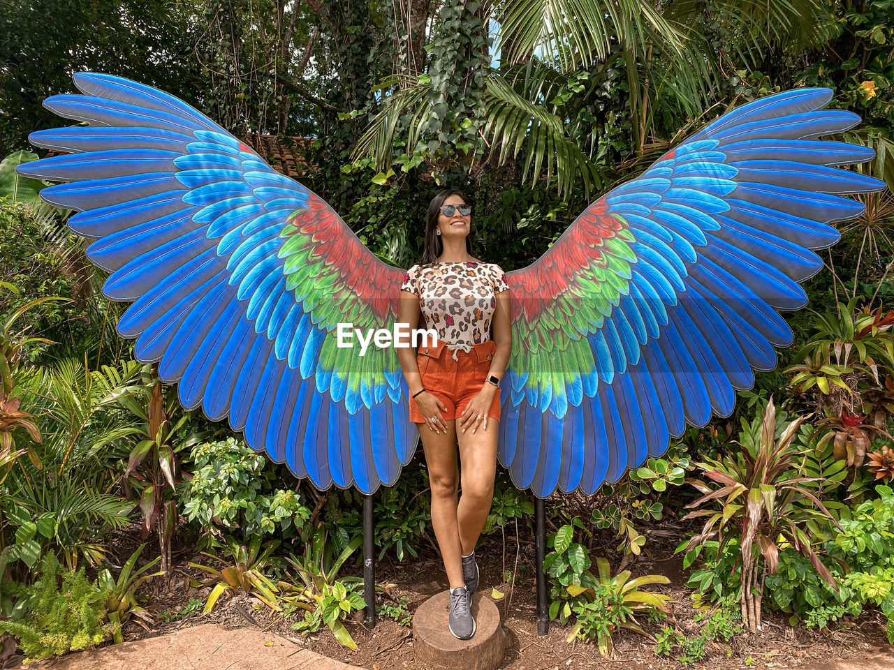 front view, full length, fashion, one person, adult, women, feather, clothing, standing, nature, portrait, beauty, young adult, multi colored, blue, looking at camera, animal wing, day, tree, beautiful woman, outdoors