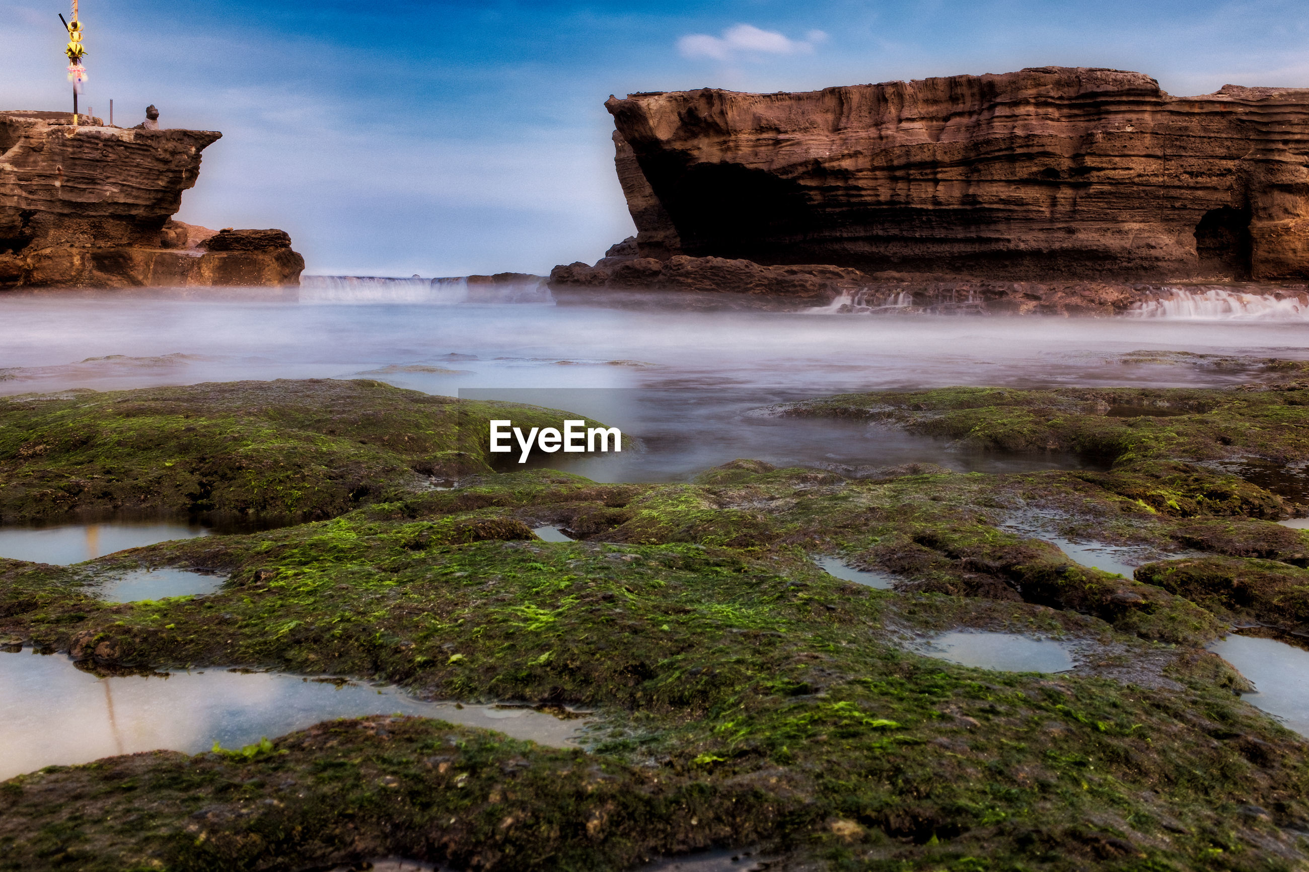 Rock formation in water against sky in bali, indonesia