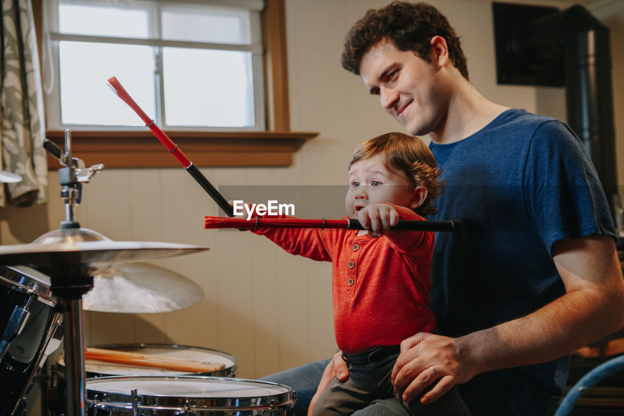 Father teaching baby boy to play drums. parent with toddler child having fun, spending time together