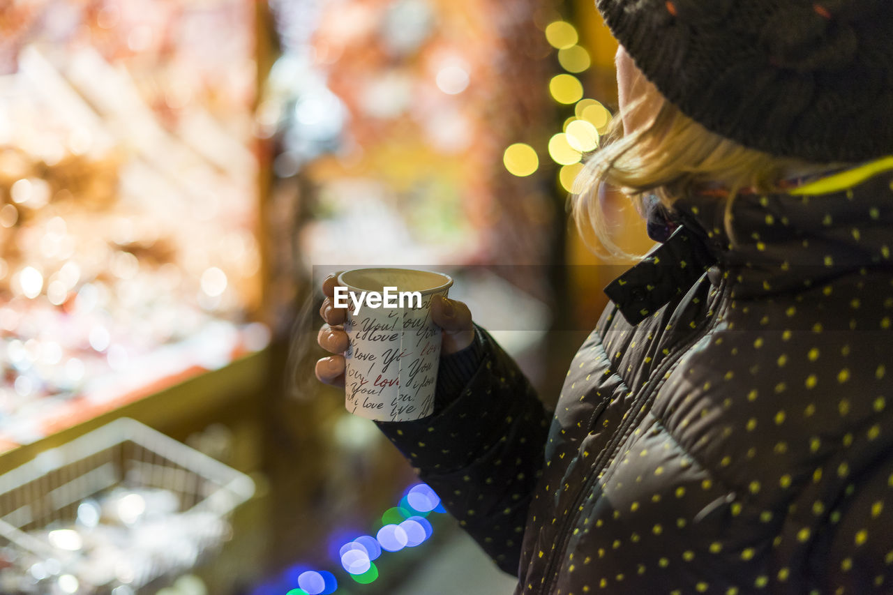 selective focus, focus on foreground, real people, close-up, refreshment, one person, drink, cup, lifestyles, illuminated, holding, leisure activity, celebration, human body part, human hand, women, hand, decoration, adult
