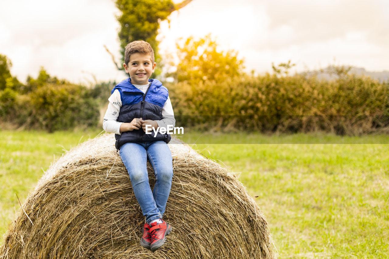 Cute boy sitting on hay bale