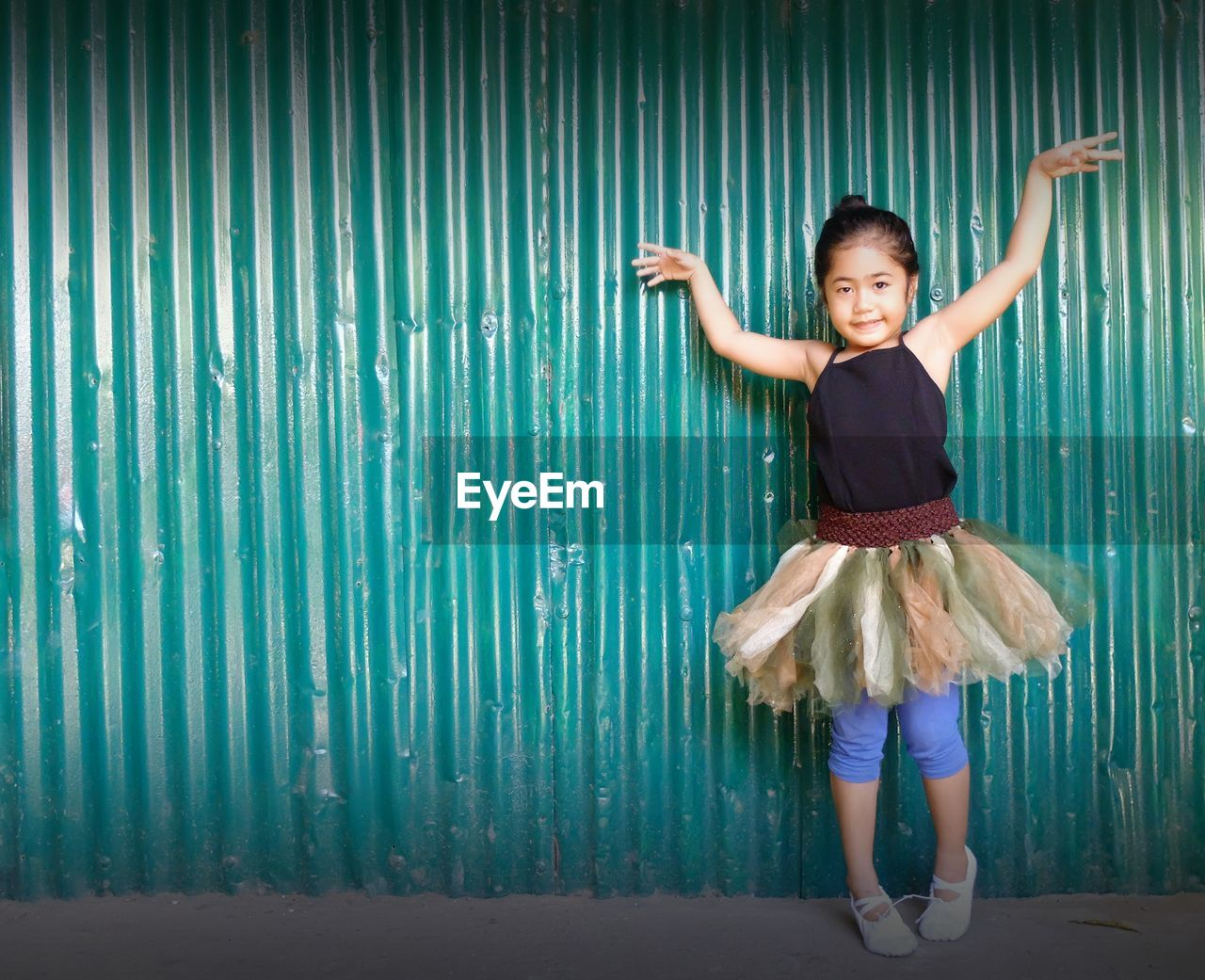 Portrait Of Cute Girl In Tutu Standing Against Wall