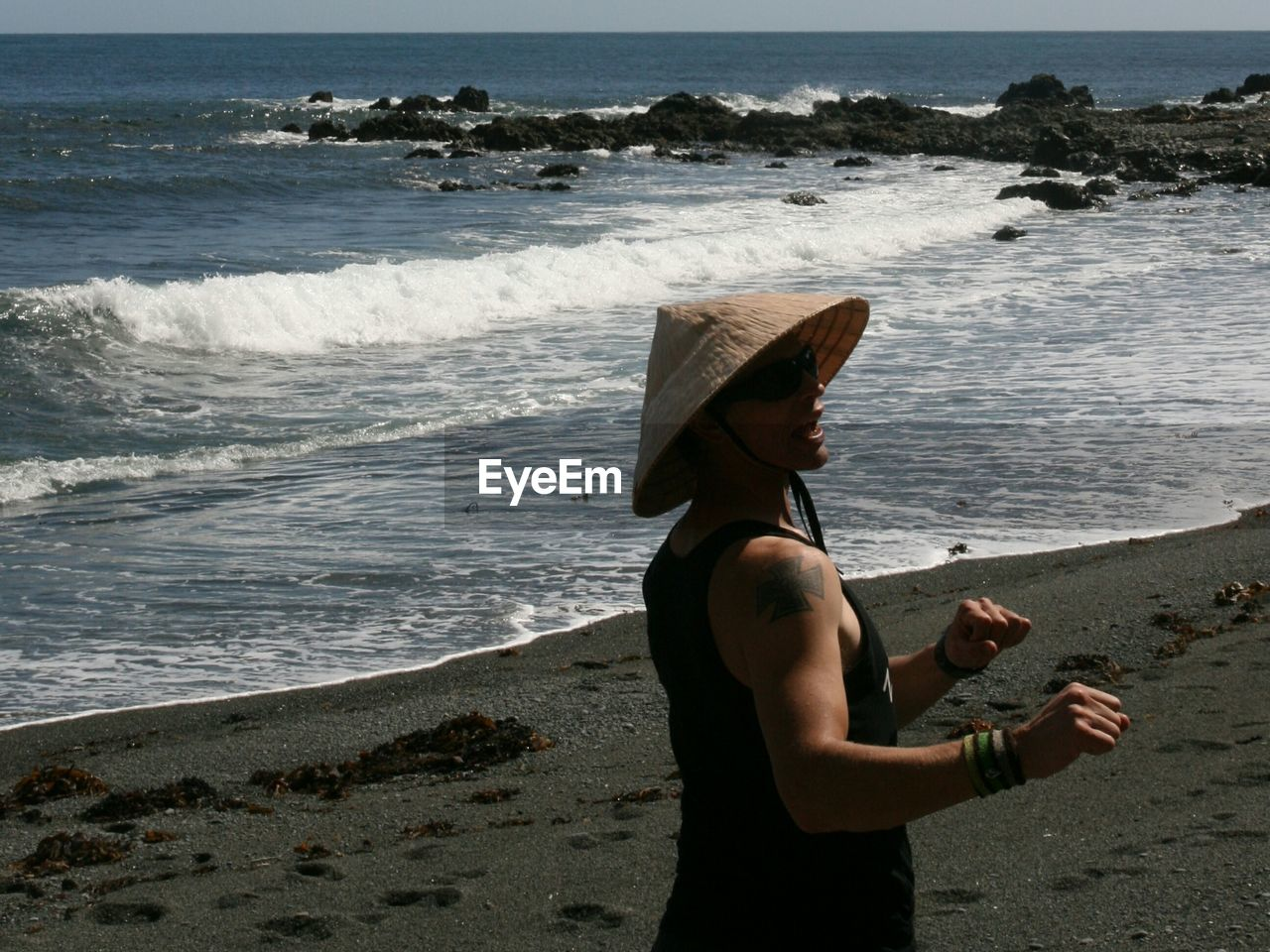 Man wearing asian style conical hat at beach