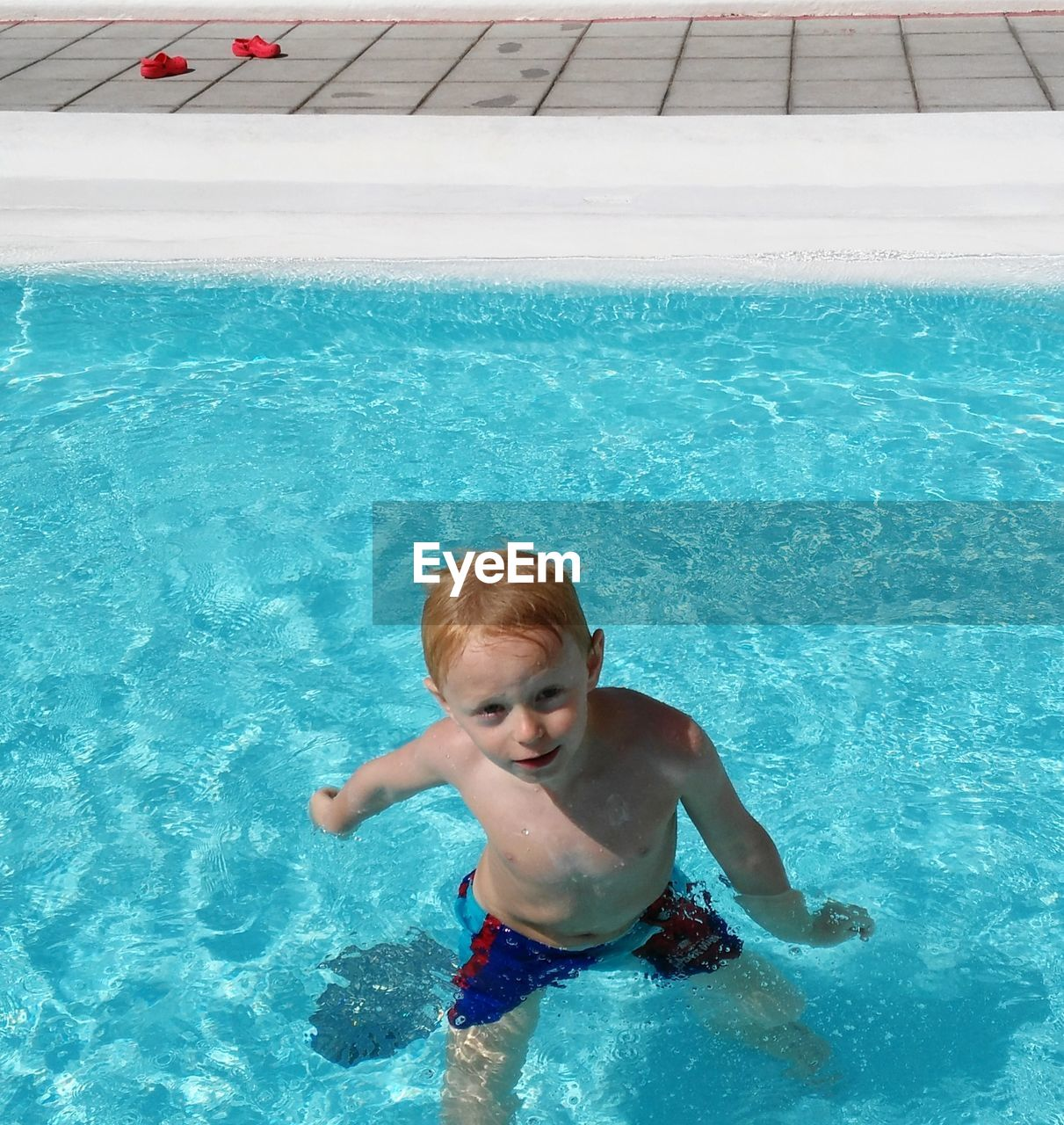 High Angle Portrait Of Boy Standing In Swimming Pool During Sunny Day