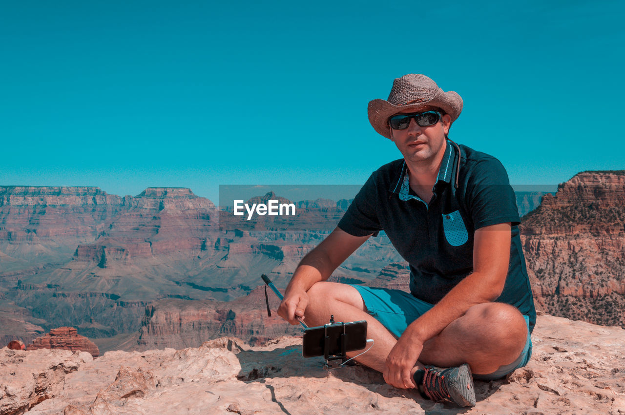 Man Sitting Against Clear Blue Sky At Grand Canyon National Park