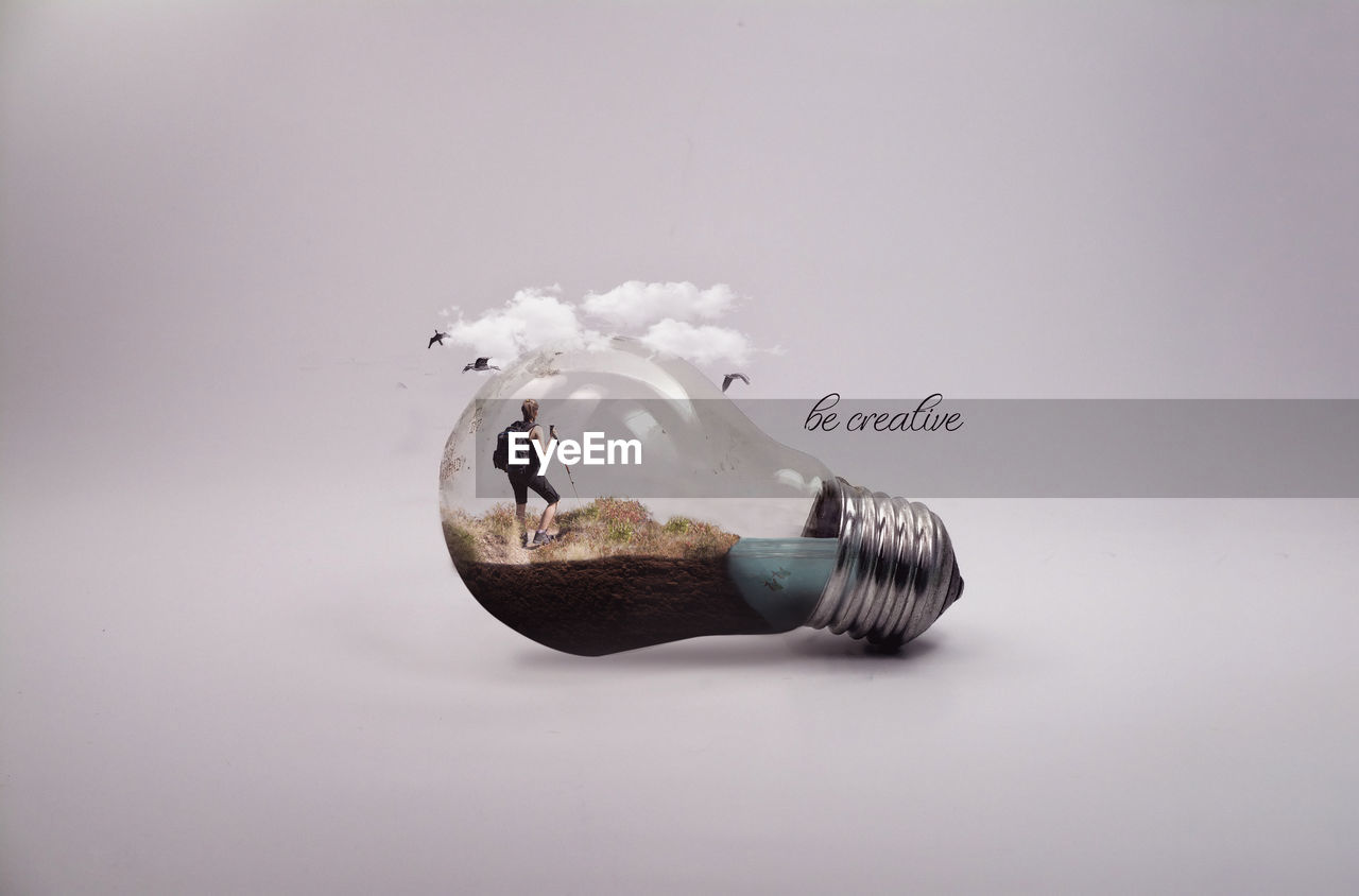 Digital composite image of woman standing on grass in light bulb