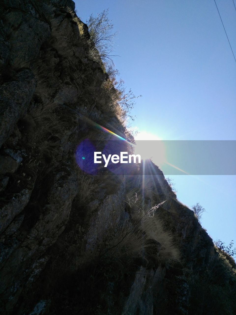 lens flare, sun, sunlight, sunbeam, low angle view, nature, blue, no people, sky, day, clear sky, outdoors, mountain, beauty in nature, scenics, tree