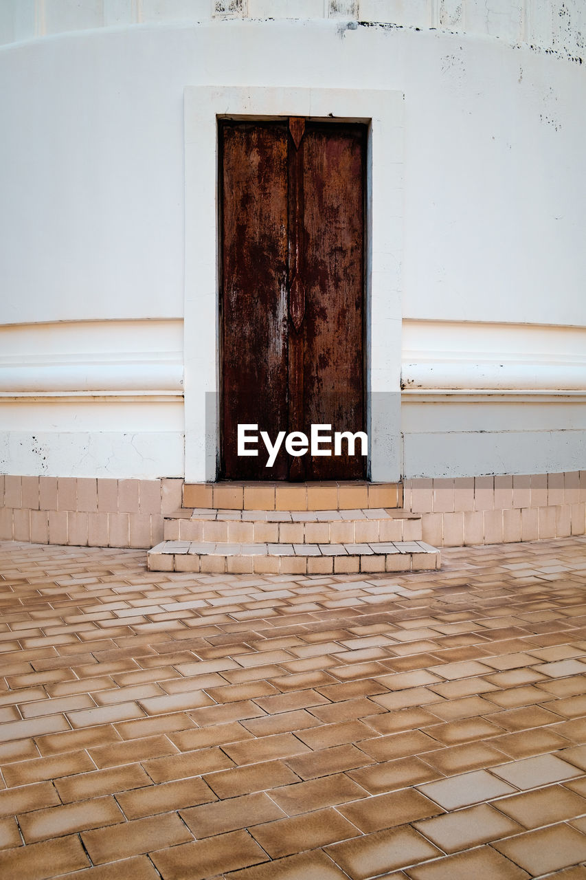 architecture, entrance, door, built structure, flooring, no people, building, building exterior, closed, wood - material, house, wall - building feature, day, pattern, brown, protection, security, outdoors, absence, tiled floor, garage