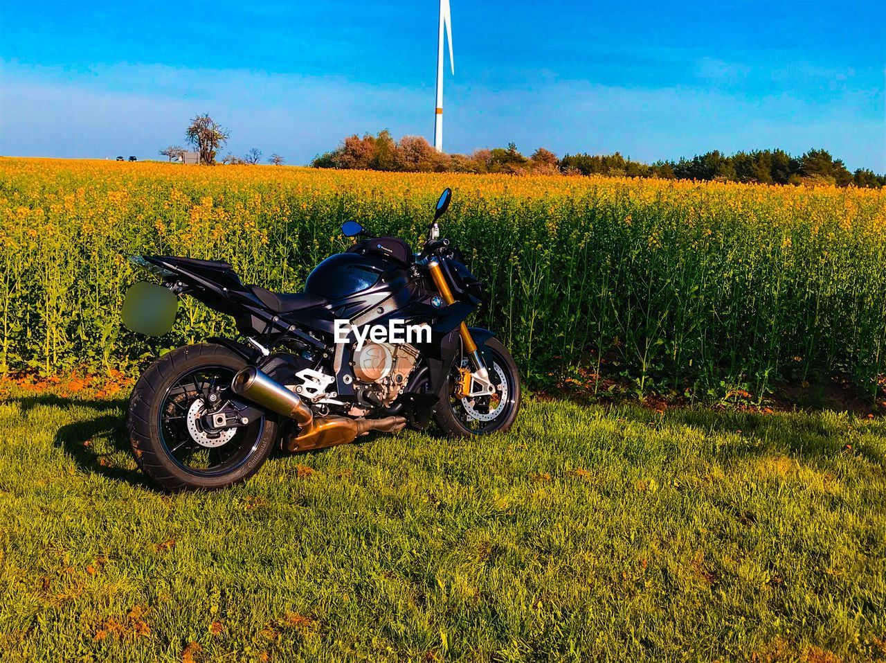 field, mode of transportation, transportation, land, plant, grass, growth, nature, landscape, land vehicle, motorcycle, day, green color, environment, no people, sky, outdoors, rural scene, beauty in nature, stationary