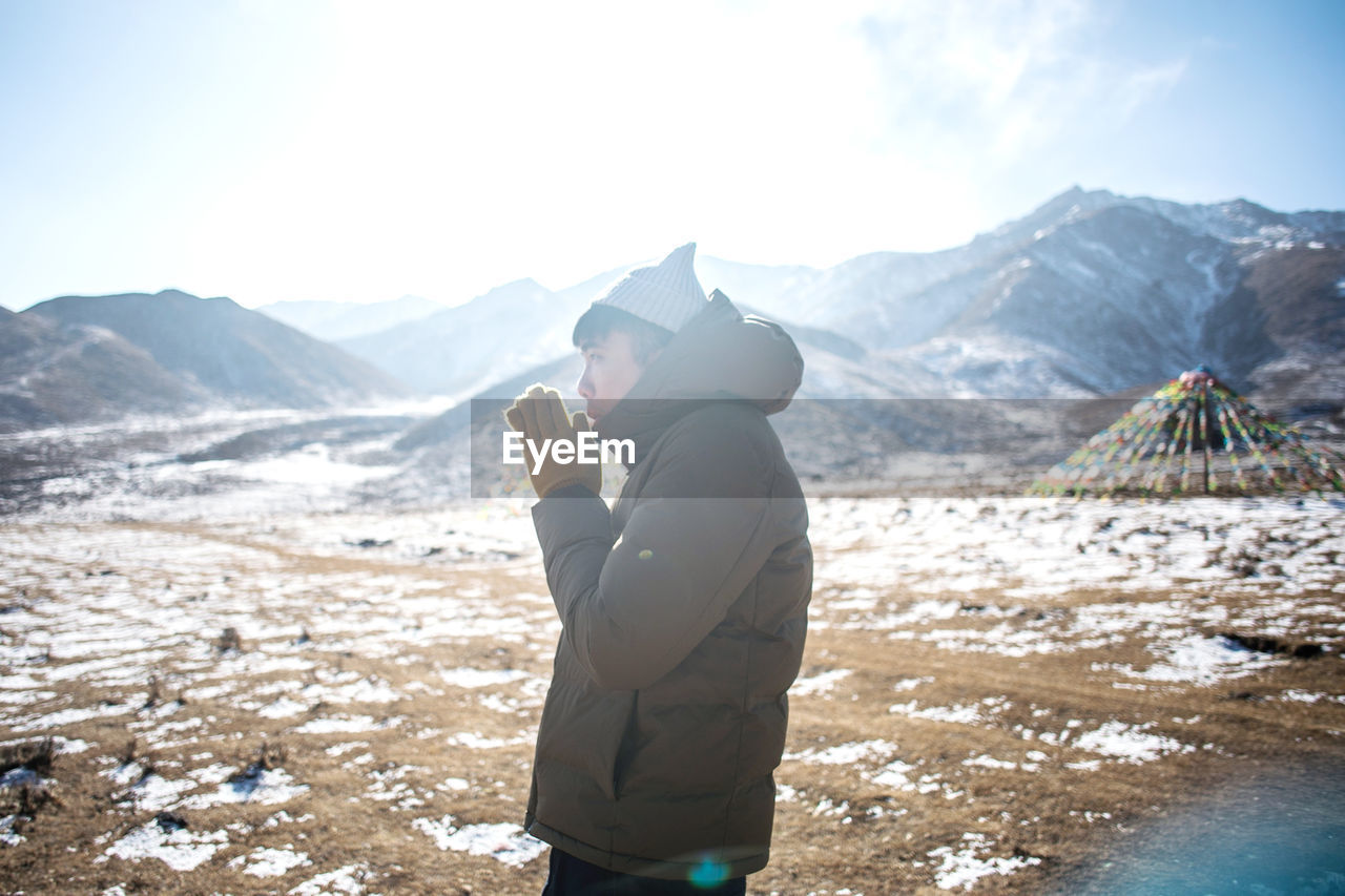 real people, mountain, beauty in nature, one person, leisure activity, mountain range, scenics - nature, lifestyles, winter, nature, sky, day, land, standing, side view, cold temperature, snow, tranquility, warm clothing, outdoors