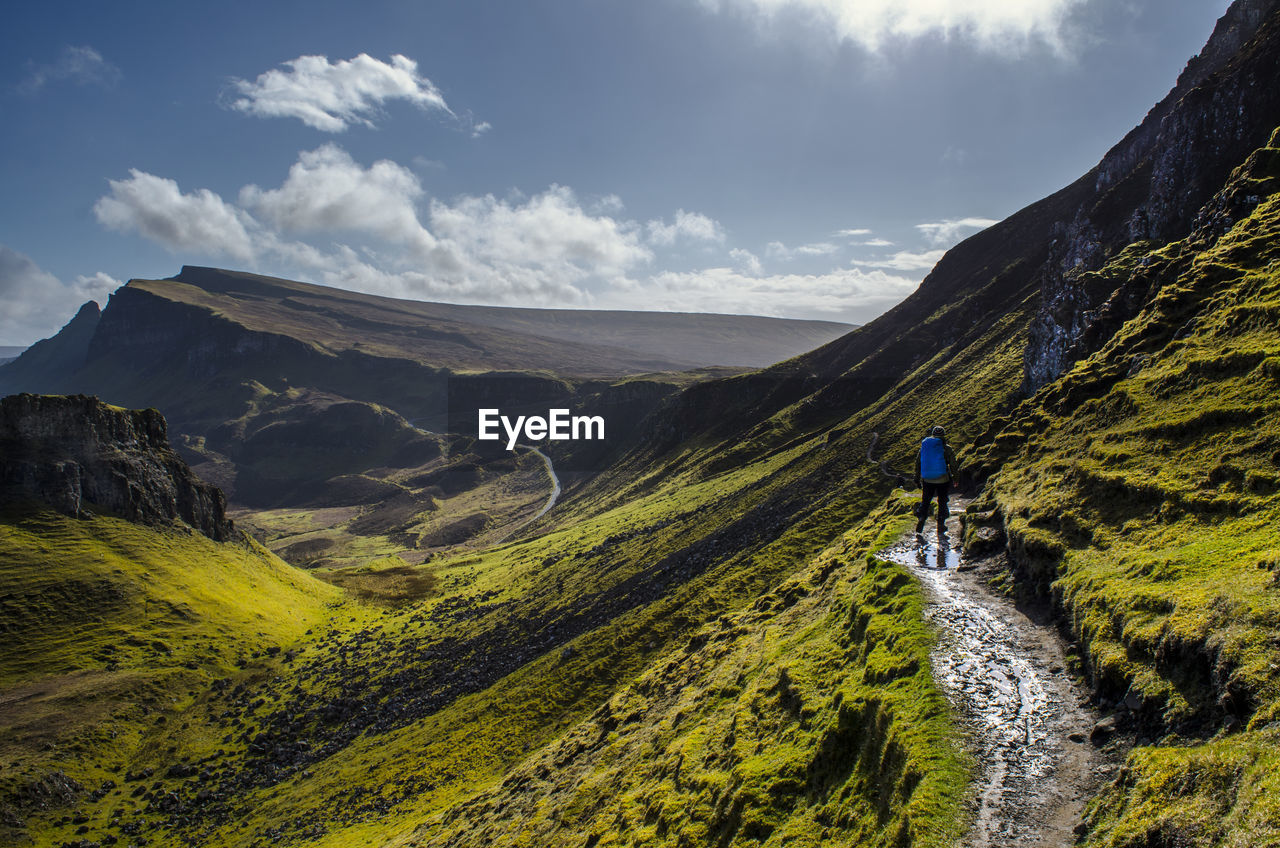 Rear View Of Man With Backpack Walking On Mountain Against Sky