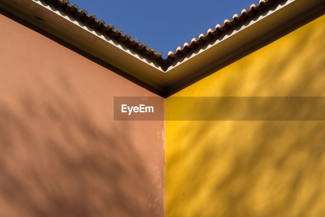 no people, low angle view, yellow, built structure, close-up, selective focus, sky, outdoors, architecture, day, nature, wall - building feature, sunlight, metal, window, pattern, building, wood - material