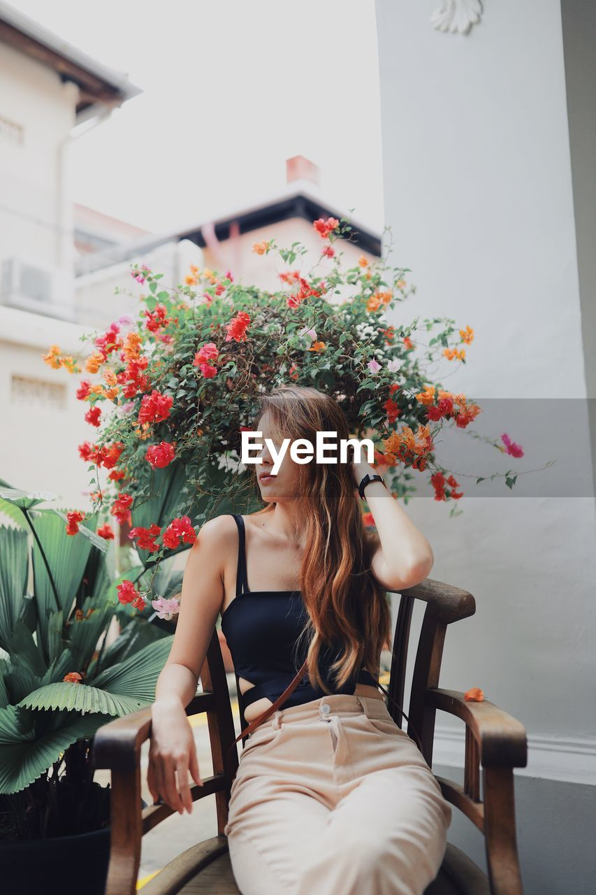Thoughtful young woman looking away while sitting on chair by potted plants