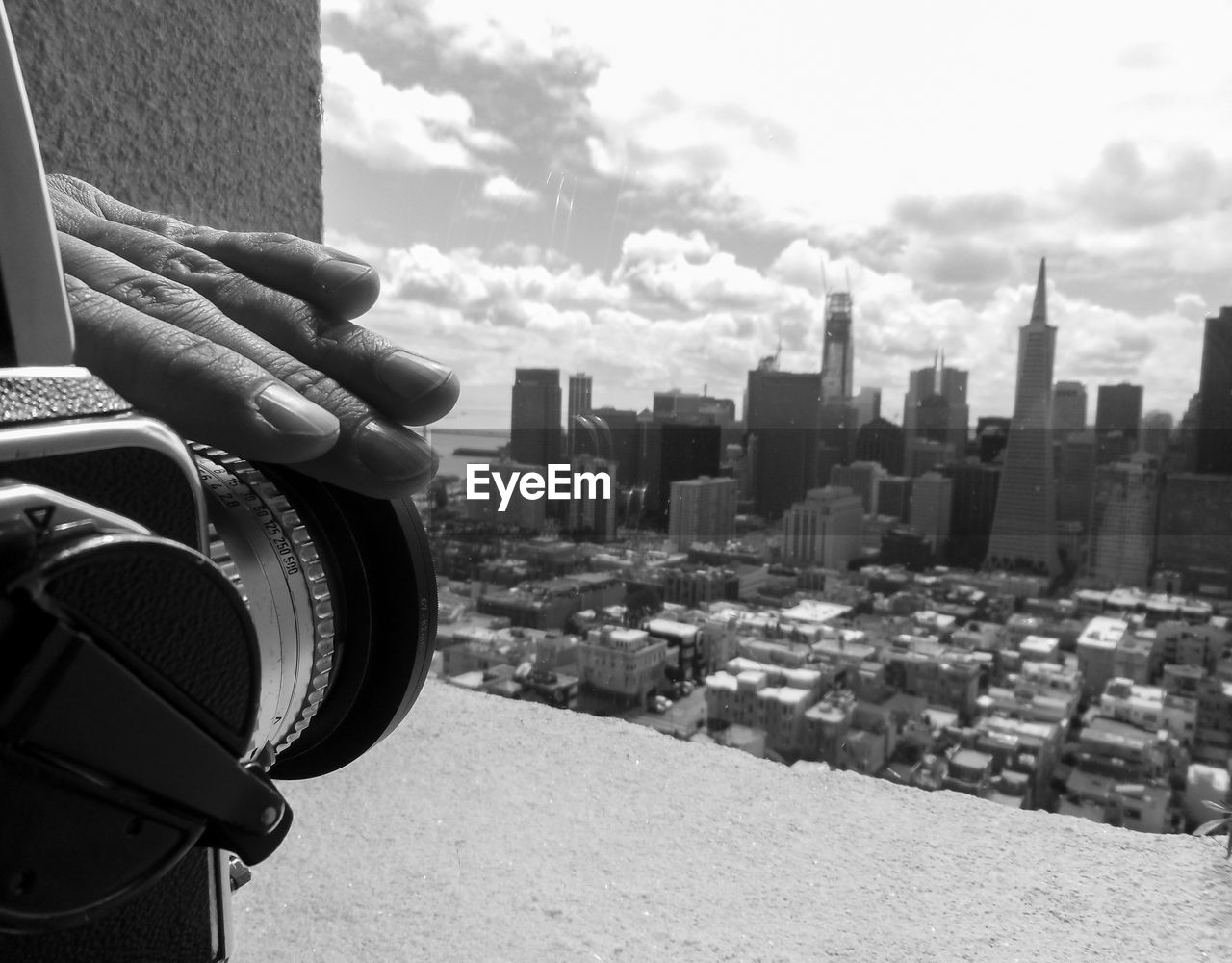 human hand, human body part, human finger, one person, real people, building exterior, architecture, holding, city, cloud - sky, built structure, outdoors, cityscape, photography themes, day, modern, skyscraper, sky, men, camera - photographic equipment, close-up, people