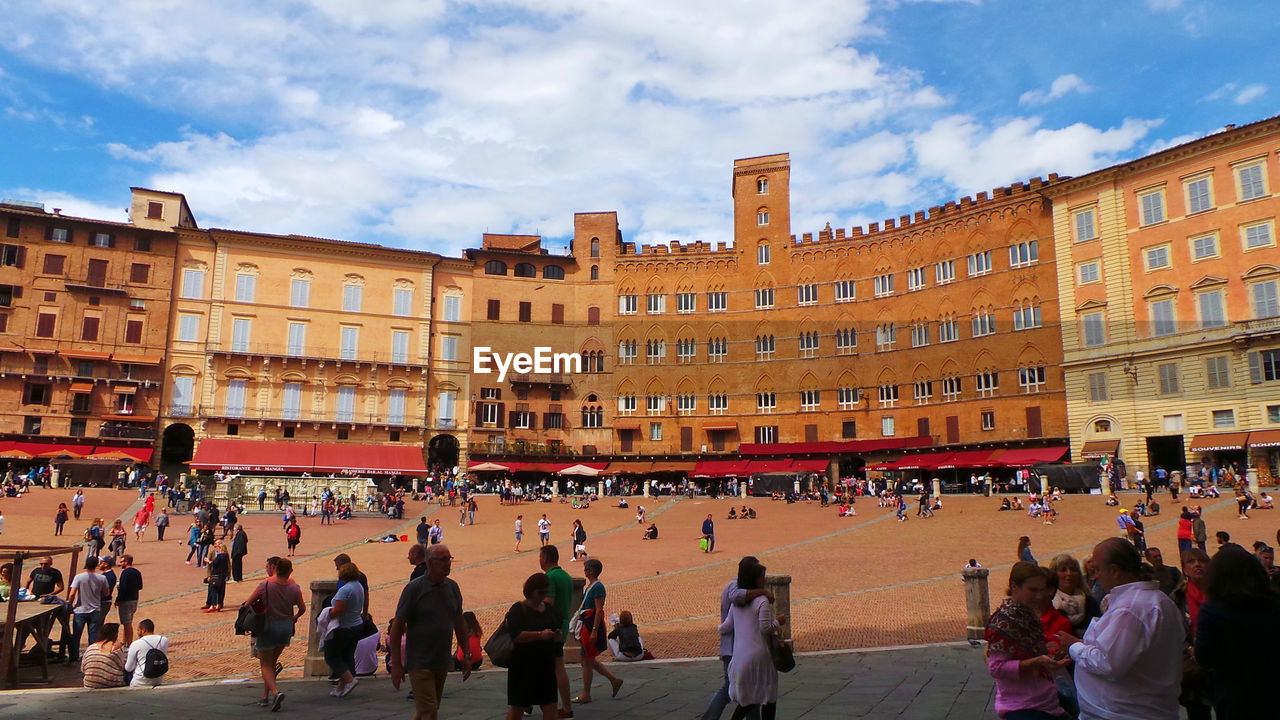 large group of people, building exterior, architecture, built structure, sky, history, cloud - sky, real people, travel destinations, day, outdoors, women, city, people