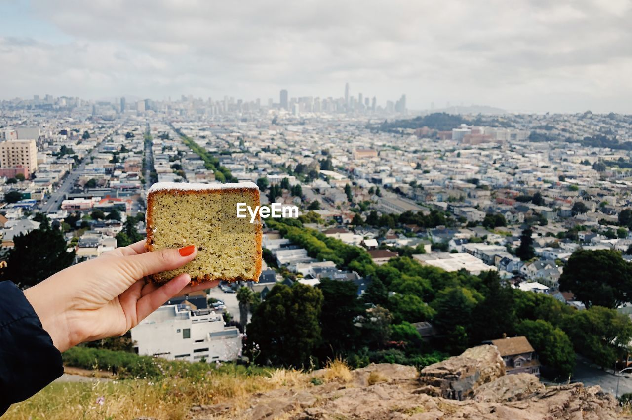 Cropped Hand Holding Bread Against City