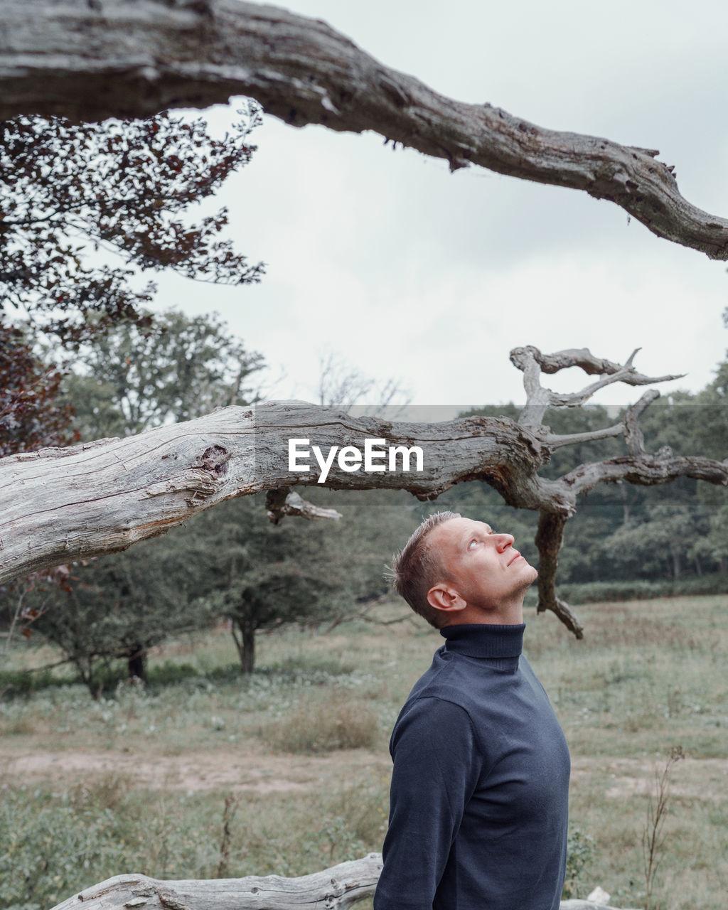 FULL LENGTH OF MAN STANDING ON FIELD AGAINST TREES