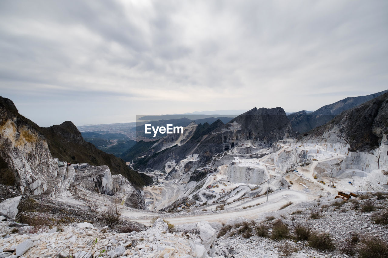 Snow covered rocky landscape against clouds