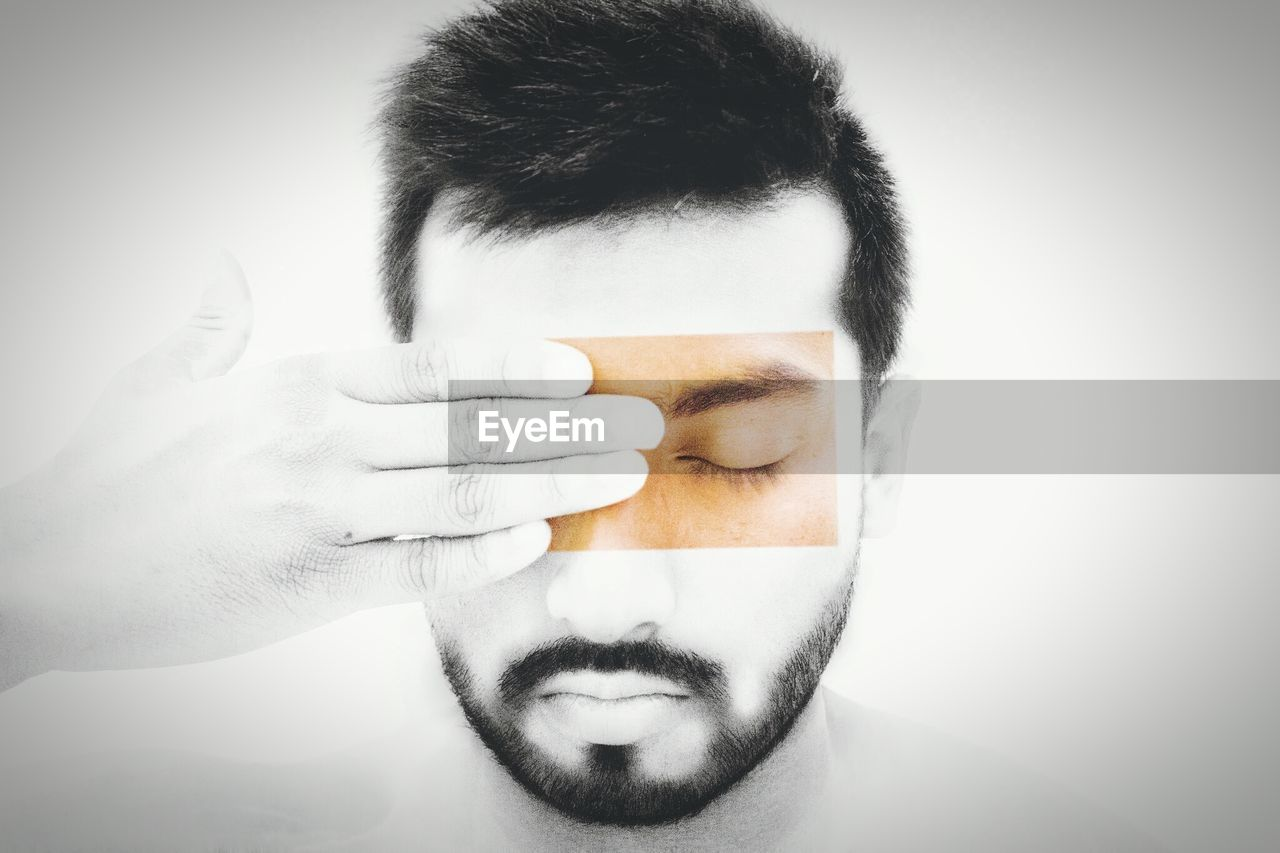 Close-up of man with hand on face against white background
