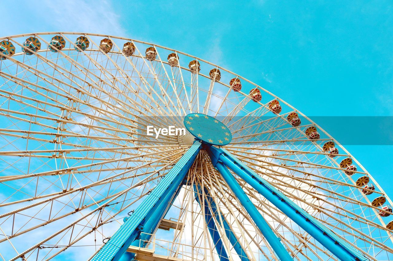 amusement park, amusement park ride, ferris wheel, sky, arts culture and entertainment, blue, low angle view, no people, architecture, built structure, nature, circle, geometric shape, day, shape, clear sky, carnival, leisure activity, fairground, outdoors