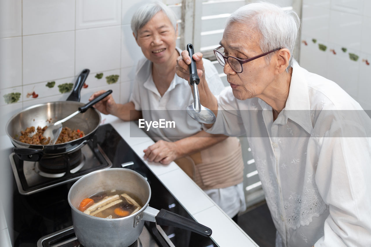 PEOPLE HAVING FOOD IN KITCHEN AT HOME
