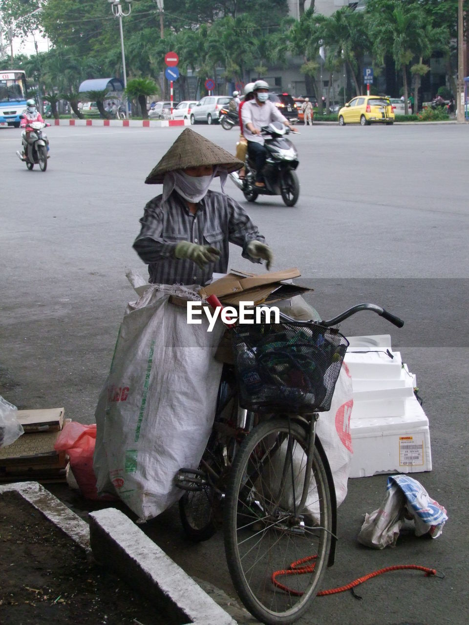 Man With Bicycle By Sacks On Road