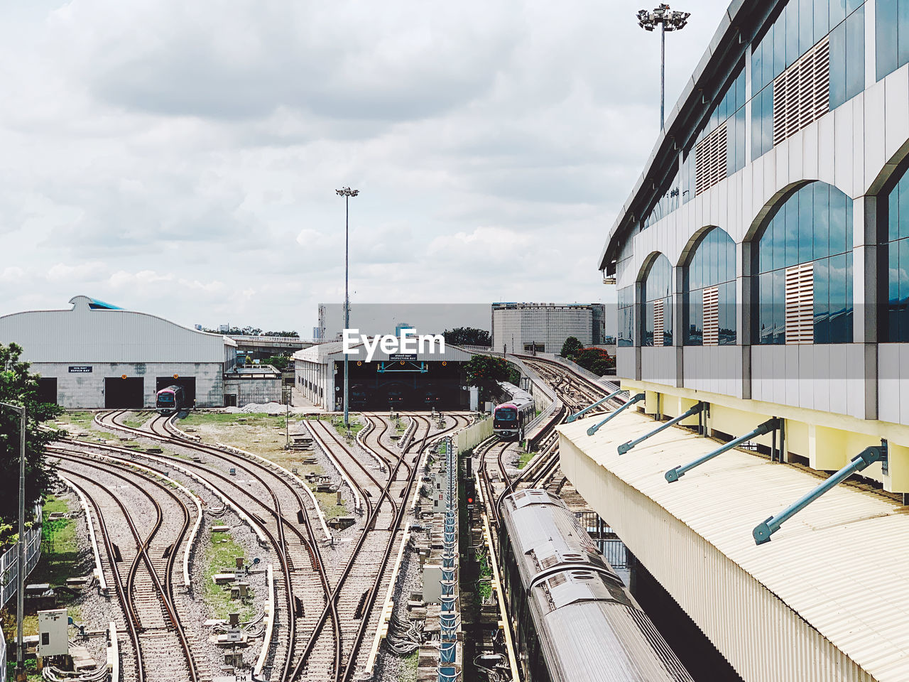 rail transportation, built structure, architecture, building exterior, track, cloud - sky, transportation, railroad track, sky, mode of transportation, train, train - vehicle, public transportation, day, nature, railroad station, city, travel, outdoors, no people, shunting yard