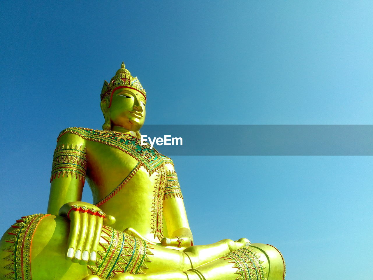 Low Angle View Of Buddha Statue Against Clear Blue Sky