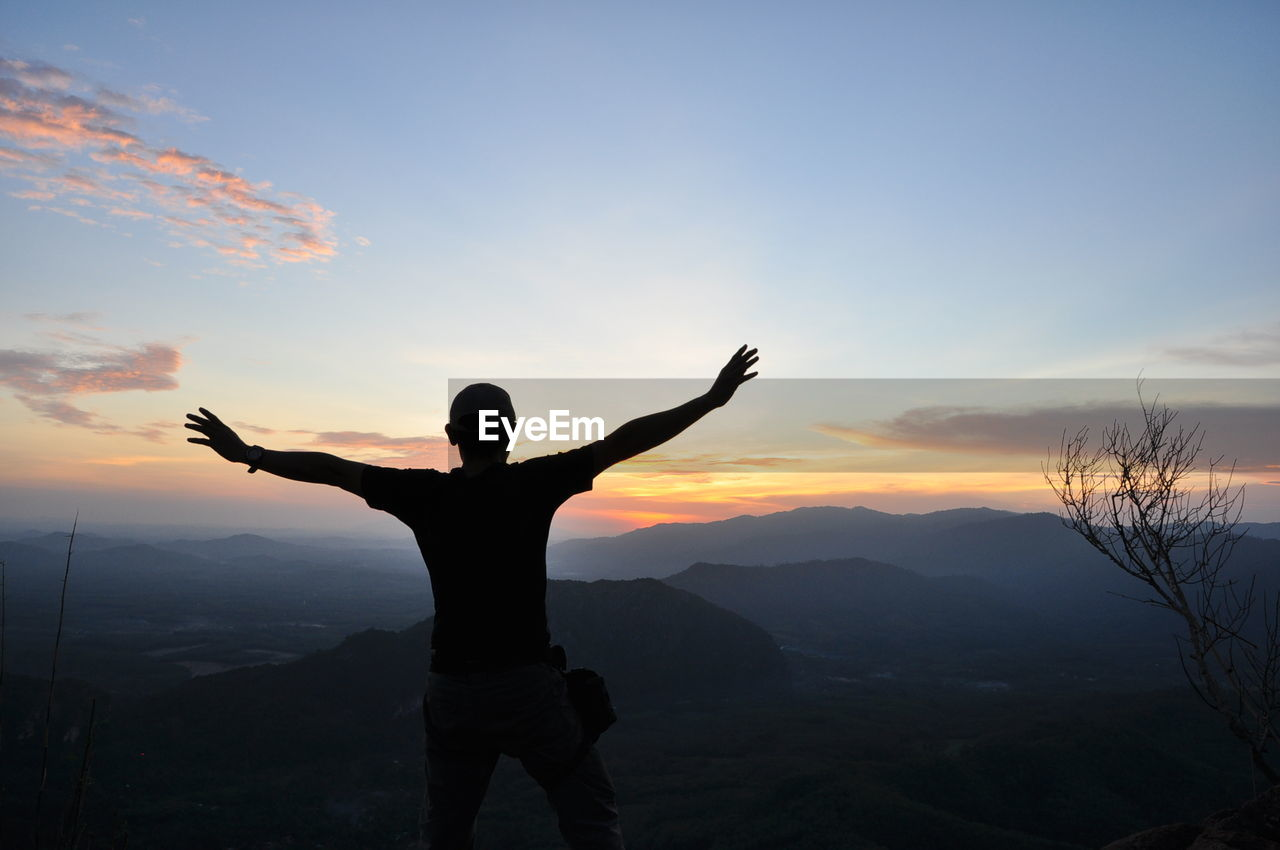 Silhouette Man With Arms Outstretched Standing On Mountain Against Sky During Sunset