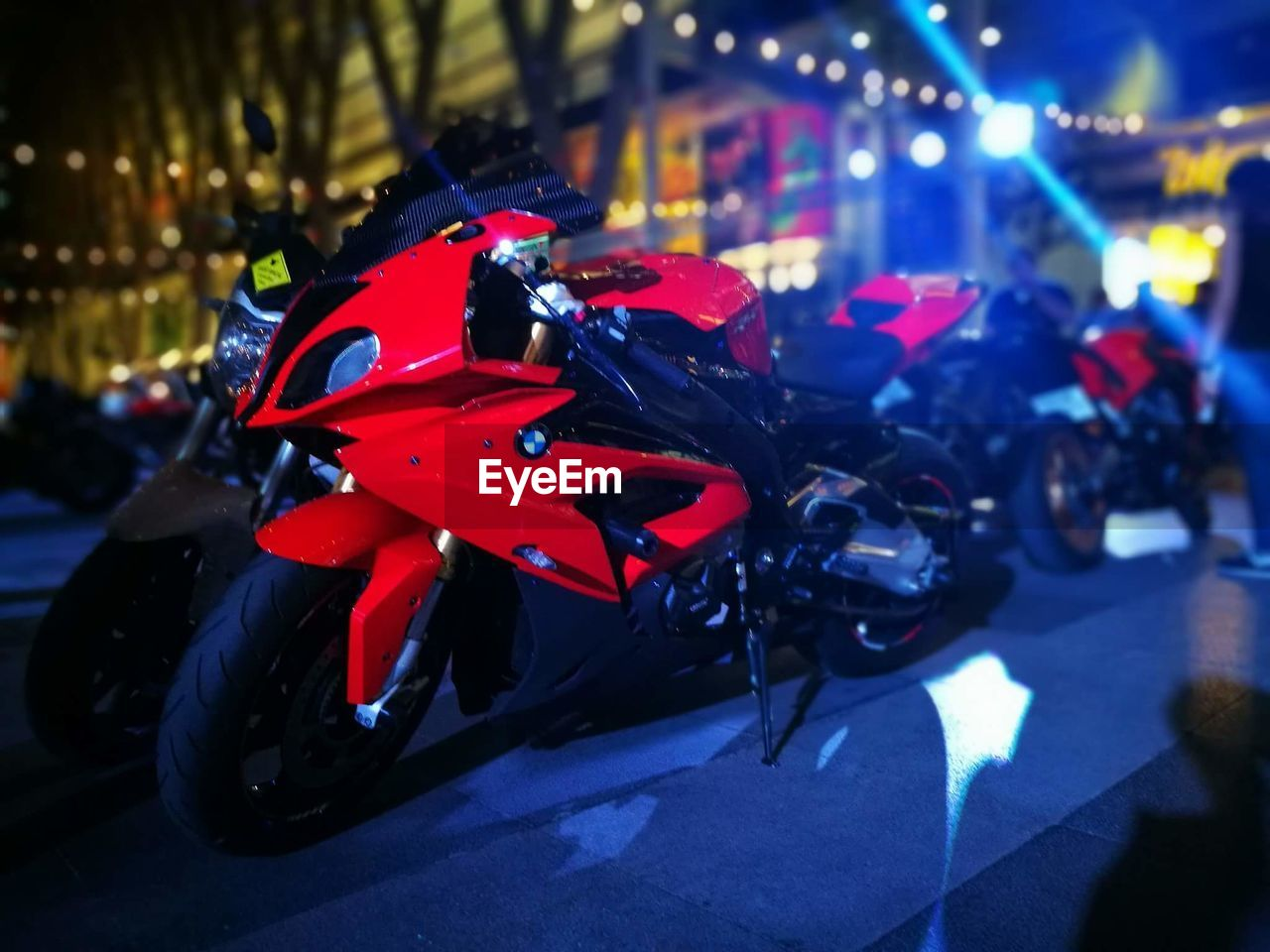land vehicle, mode of transport, transportation, night, motorcycle, illuminated, red, focus on foreground, outdoors, stationary, scooter, no people, city, close-up