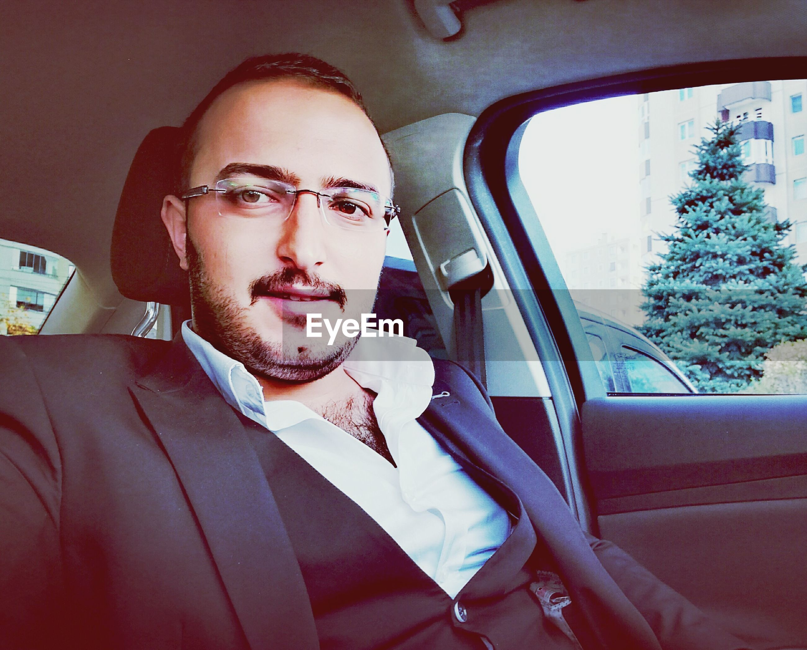 car, only men, one man only, one person, business, car interior, adults only, businessman, young adult, one young man only, vehicle interior, headshot, transportation, eyeglasses, driving, adult, people, men, well-dressed, portrait, close-up, day