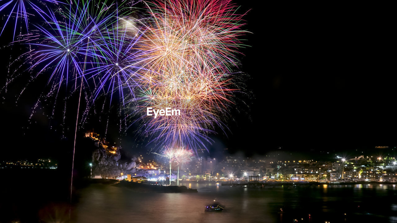night, illuminated, water, firework, motion, celebration, architecture, firework display, event, building exterior, arts culture and entertainment, city, built structure, nature, reflection, exploding, sky, river, no people, cityscape, light, outdoors, firework - man made object