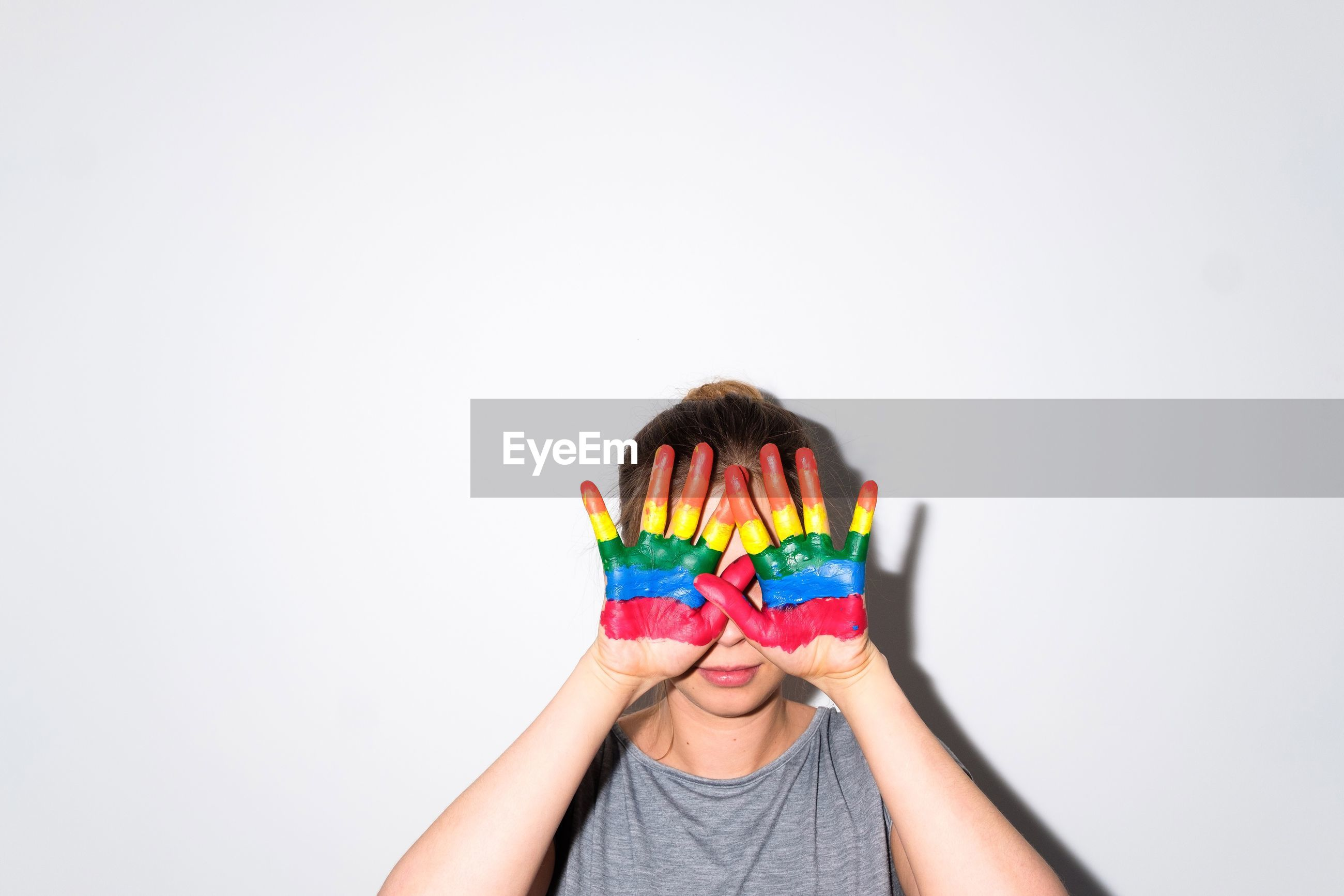 Young woman with colorful painted hands covering face while standing against wall