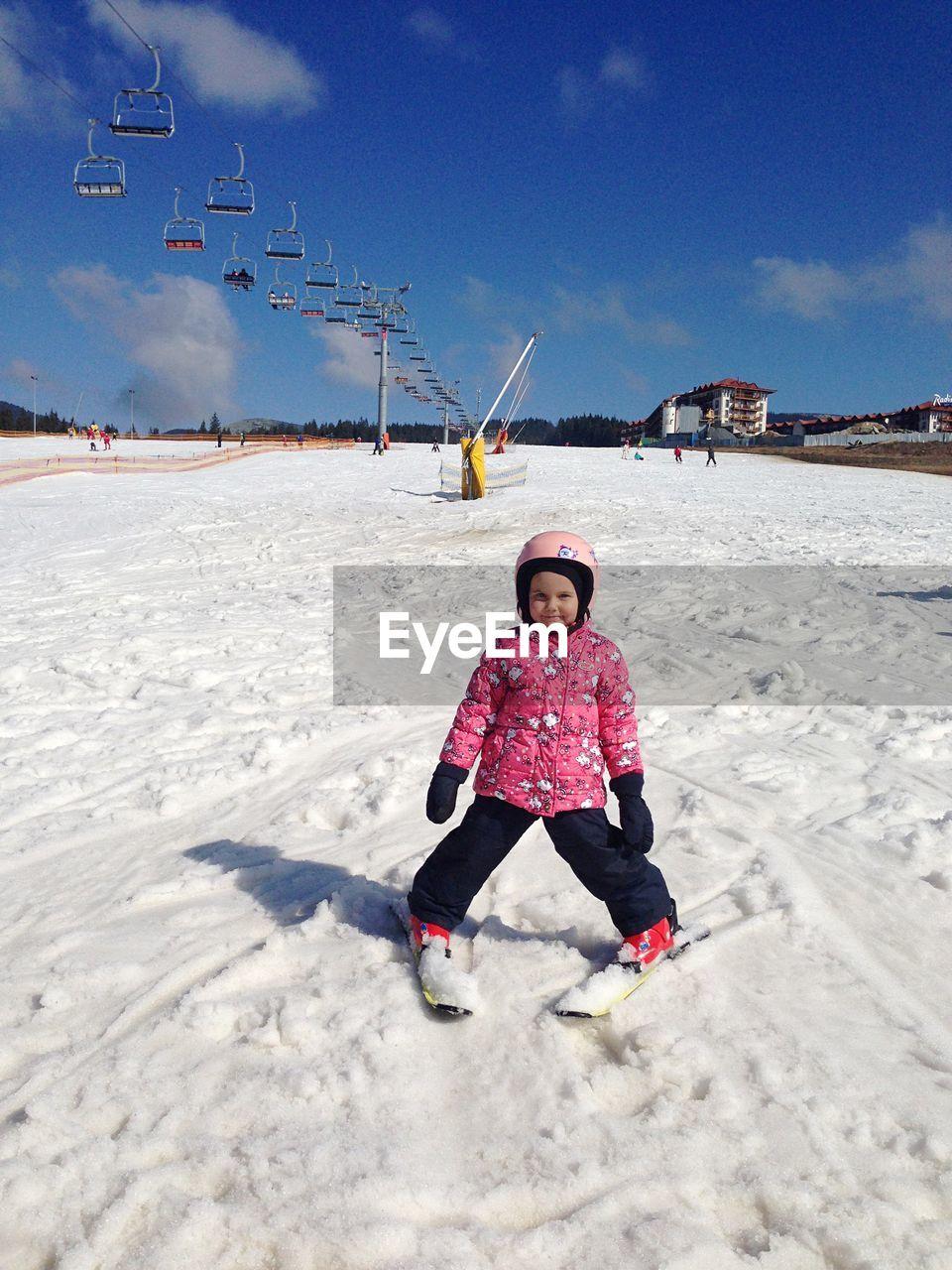 Portrait Of Girl Skiing On Snow Against Sky