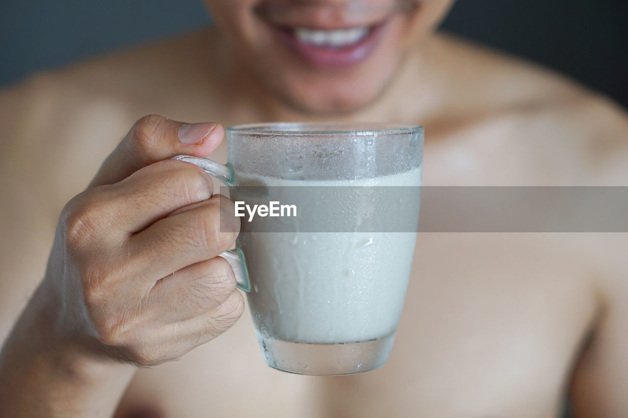 Midsection of man having milk