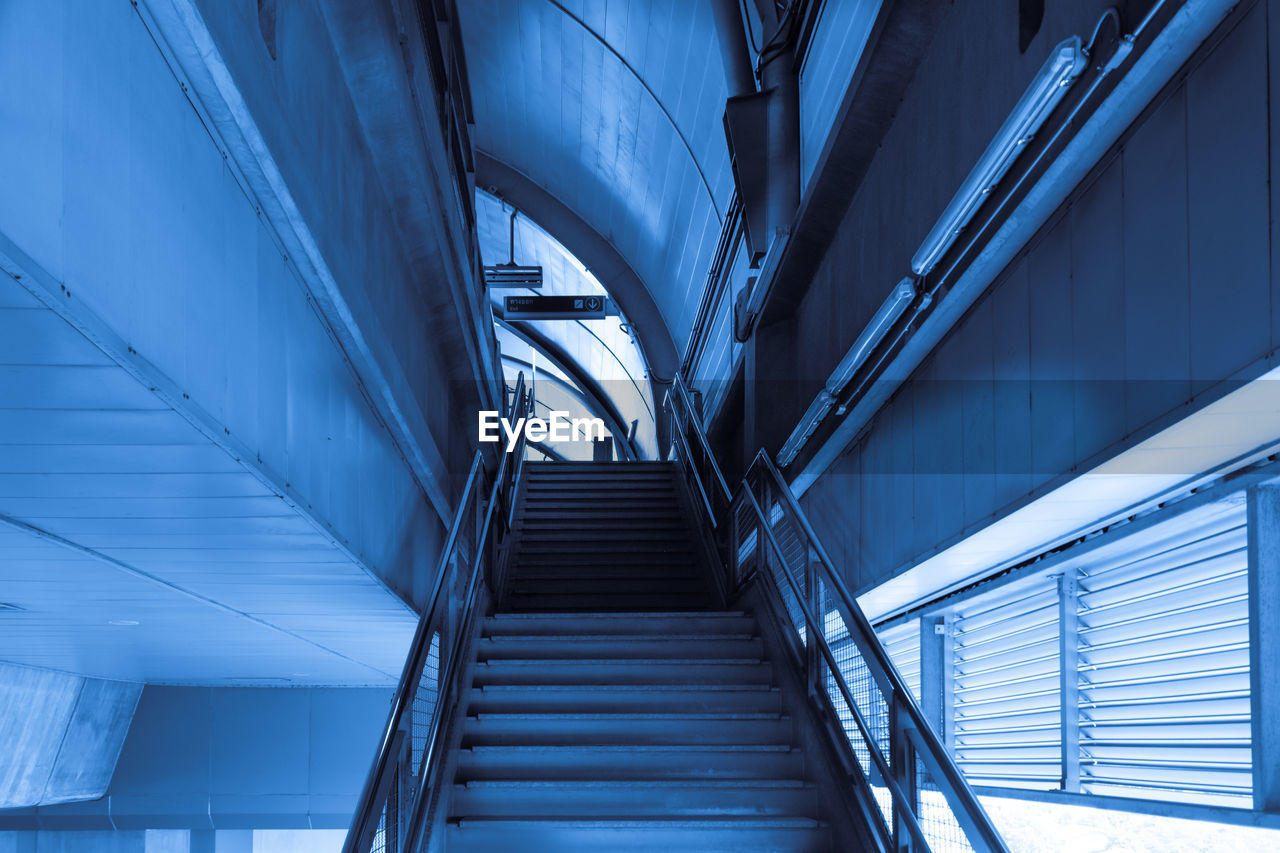 architecture, staircase, steps and staircases, built structure, low angle view, railing, indoors, no people, day, modern, direction, the way forward, transportation, building, pattern, connection, blue, sunlight, nature, ceiling