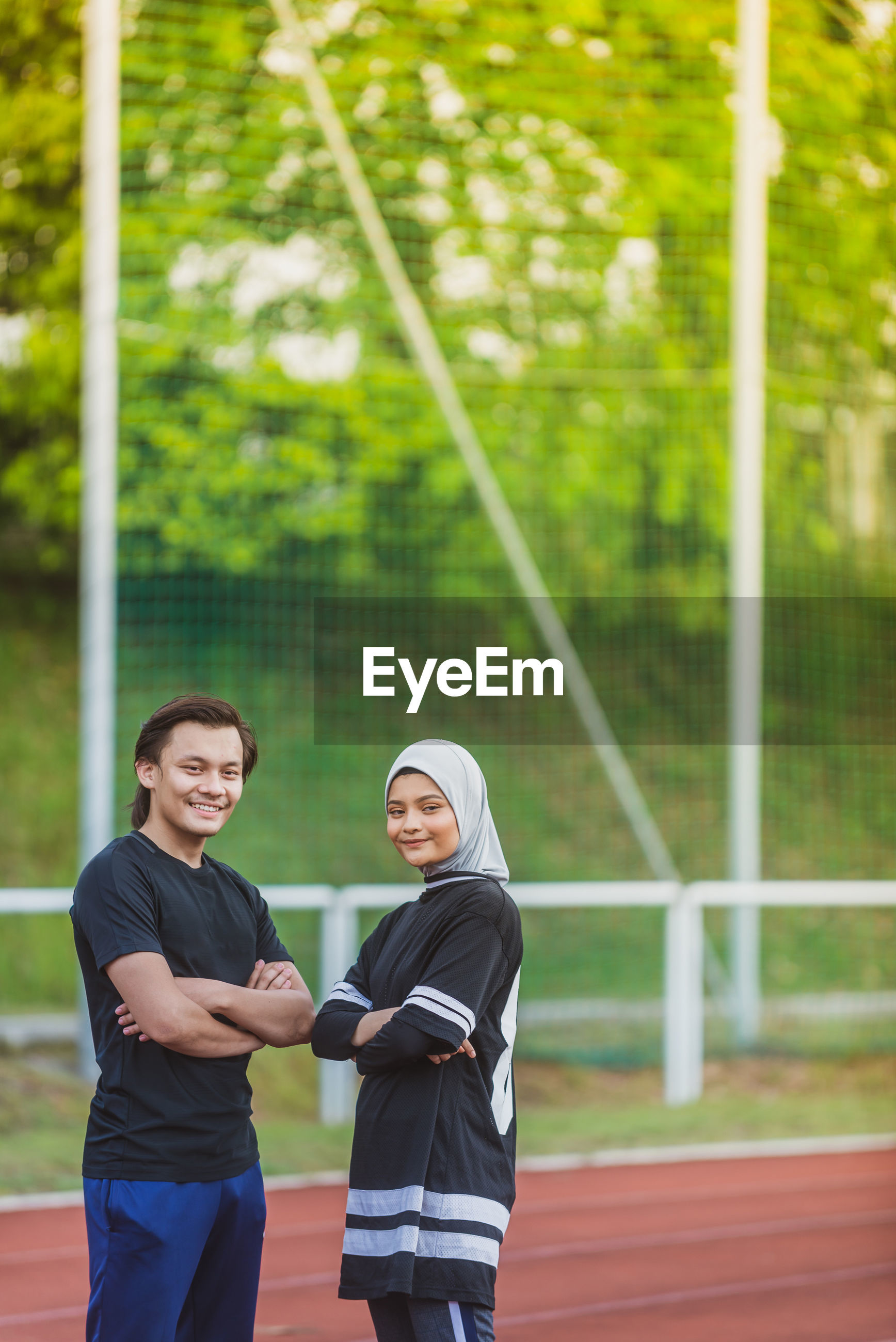 Portrait of couple standing on running track