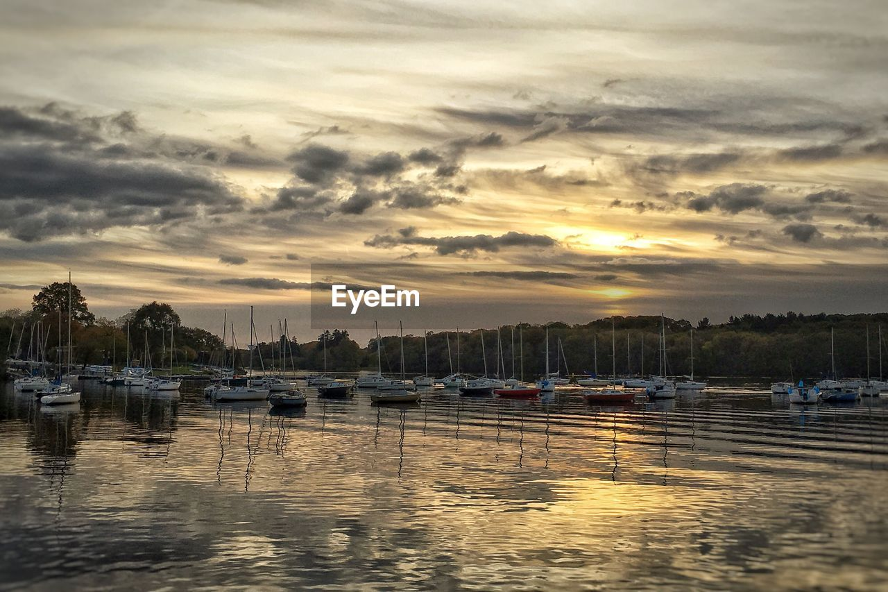 sunset, water, reflection, sky, cloud - sky, nautical vessel, dramatic sky, transportation, waterfront, mode of transport, no people, nature, scenics, moored, tranquility, beauty in nature, travel destinations, tranquil scene, outdoors, lake, architecture, built structure, building exterior, yacht, city, tree, harbor, day
