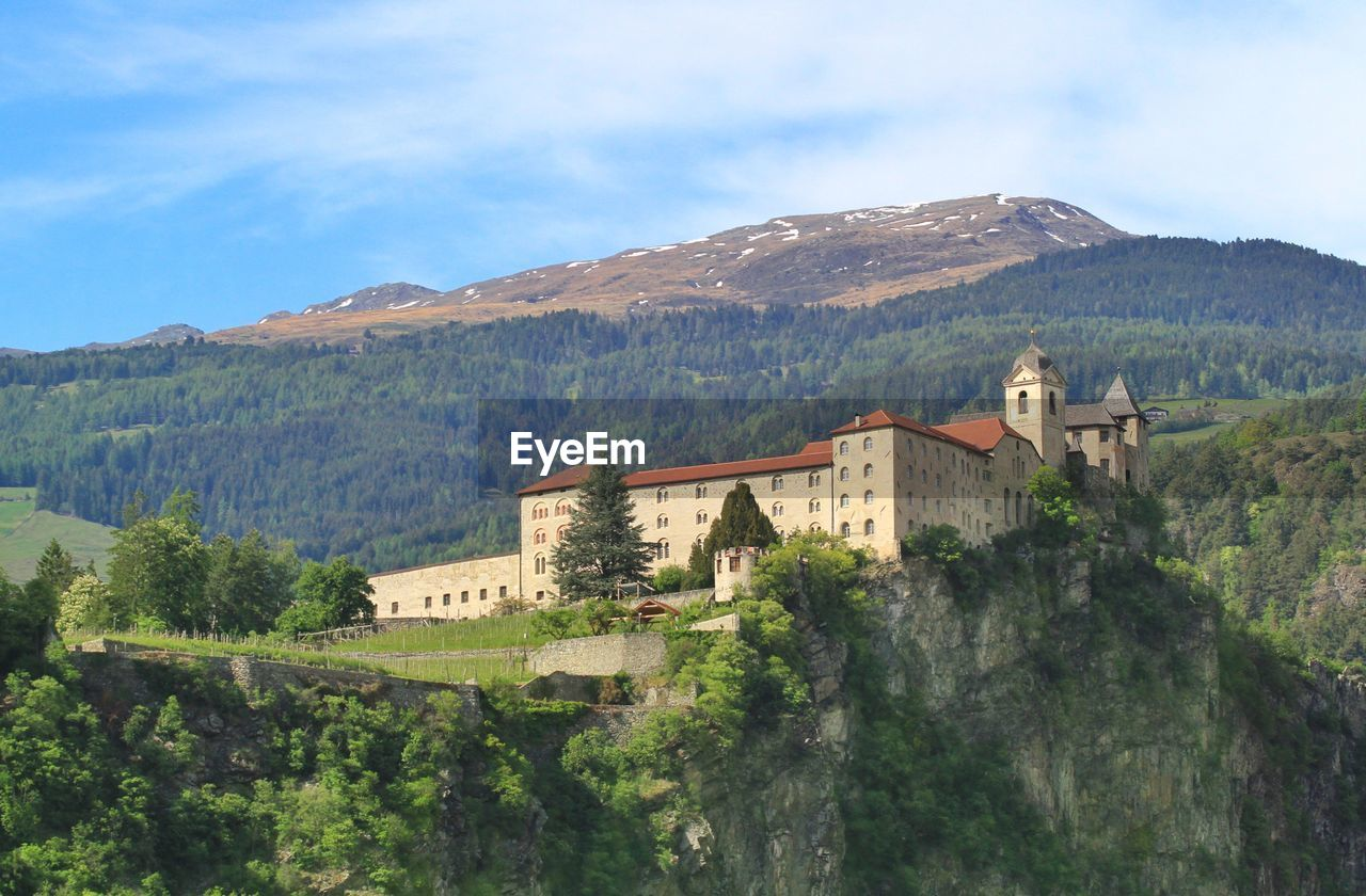 mountain, architecture, built structure, building exterior, sky, building, tree, nature, plant, scenics - nature, day, cloud - sky, mountain range, beauty in nature, environment, history, landscape, no people, land, the past, outdoors
