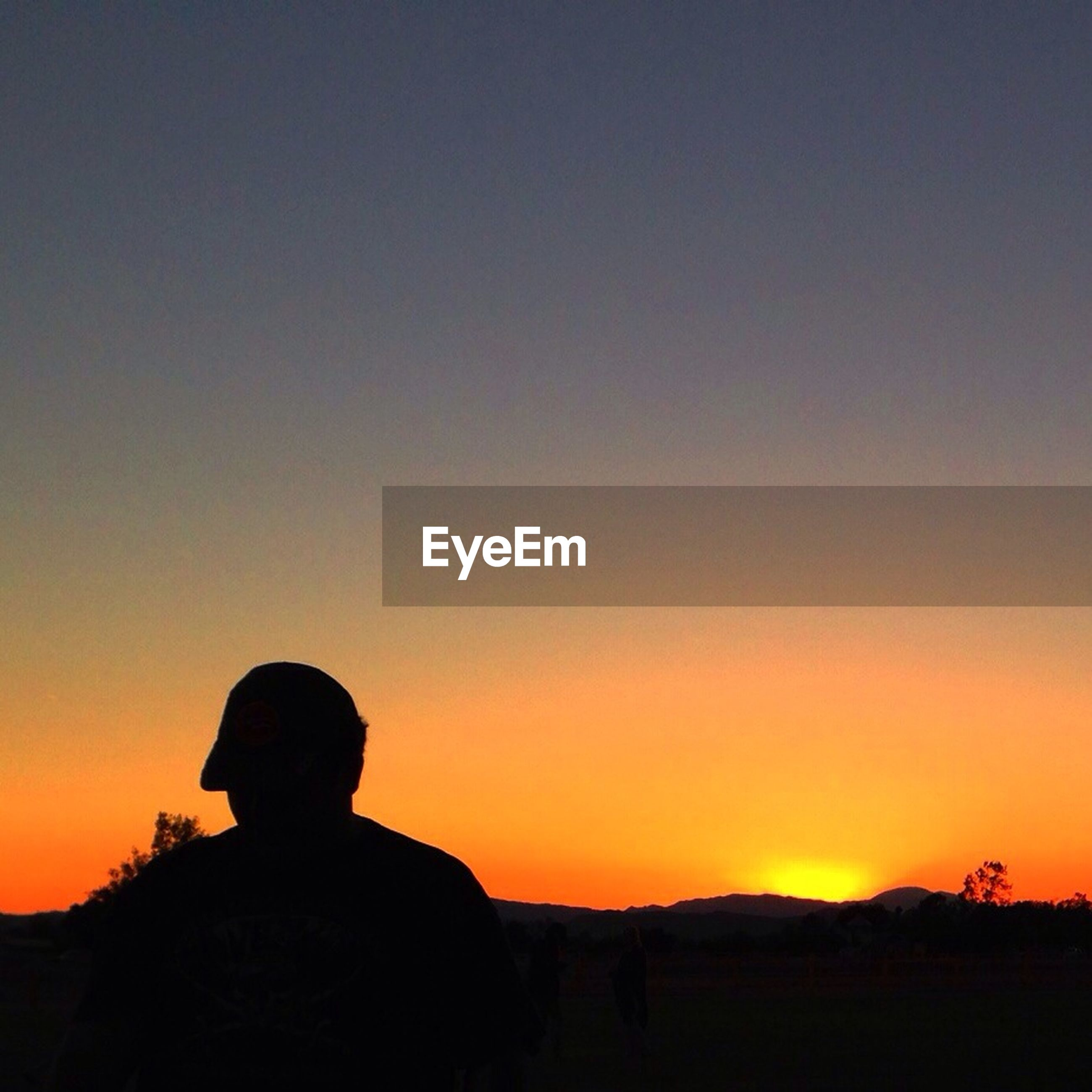 SILHOUETTE OF PEOPLE ON LANDSCAPE AT SUNSET